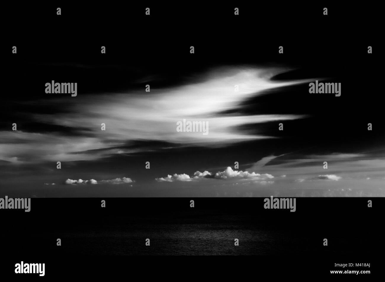 L'image monochrome à fort contraste contemporain de substitution, les formations nuageuses sur une mer calme. Banque D'Images