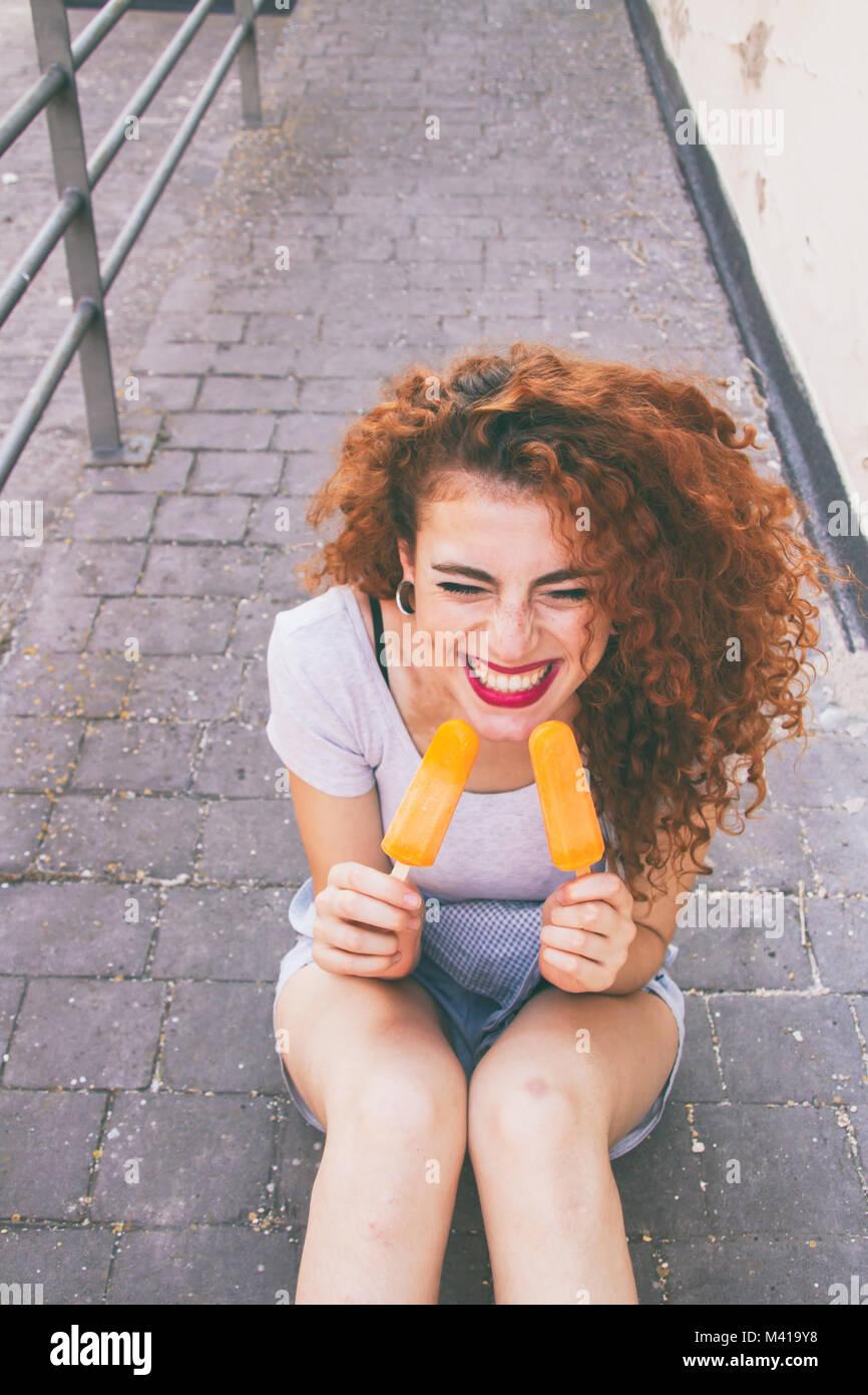 Jeune femme rousse de manger des glaces en été Photo Stock