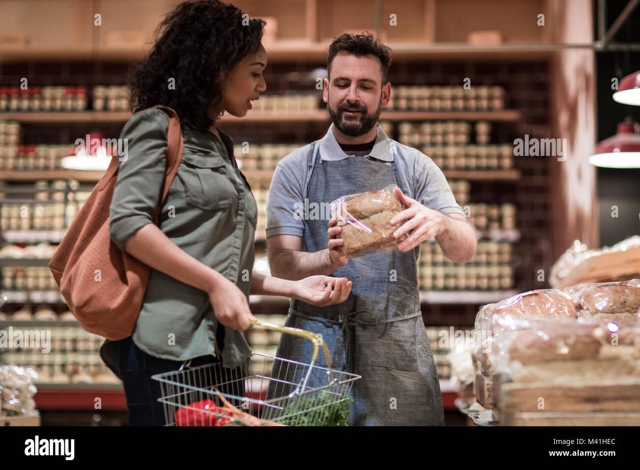 Baker helping customer in grocery store Banque D'Images