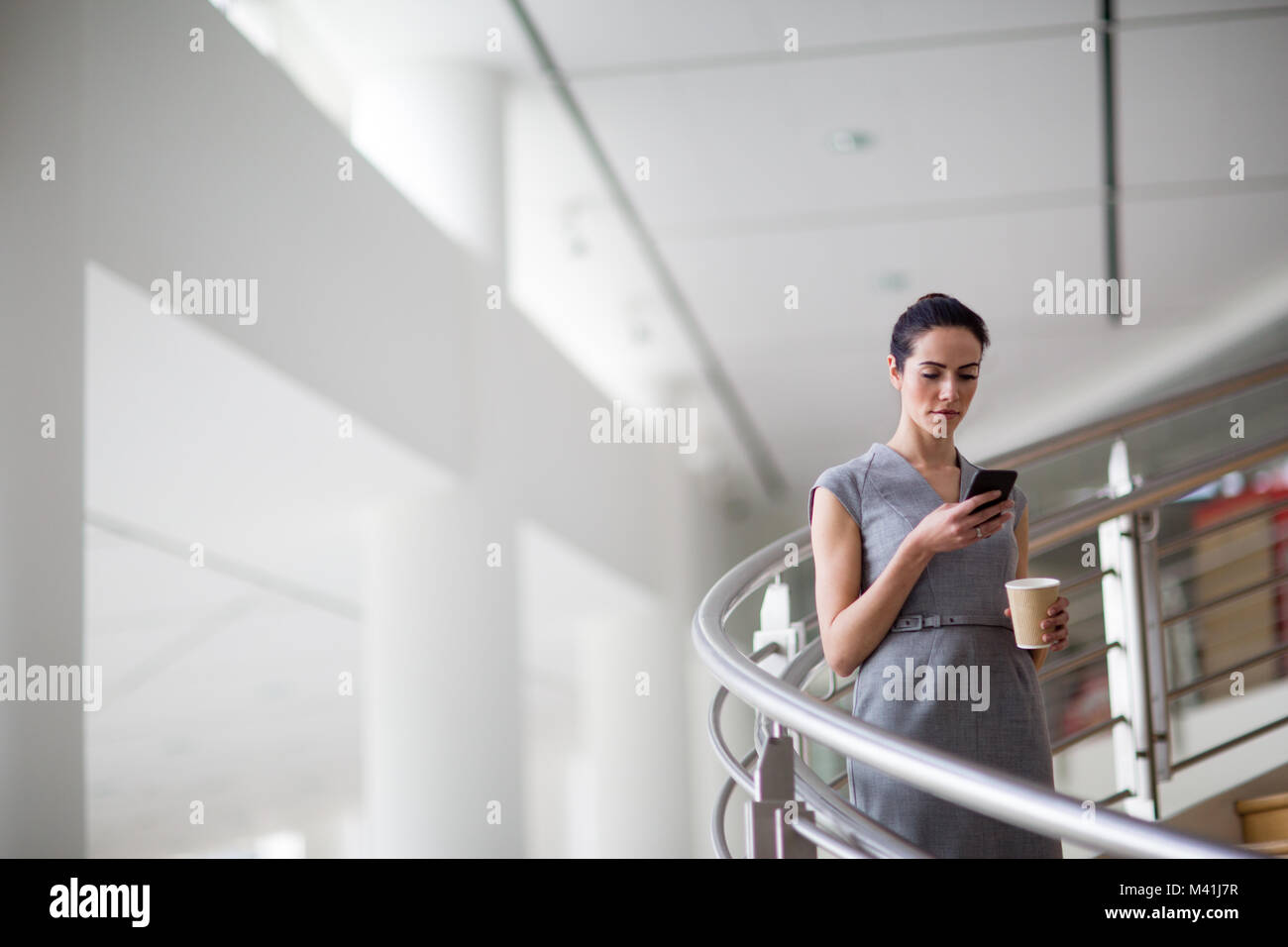 Businesswoman using smartphone app sur sa façon de travailler Photo Stock