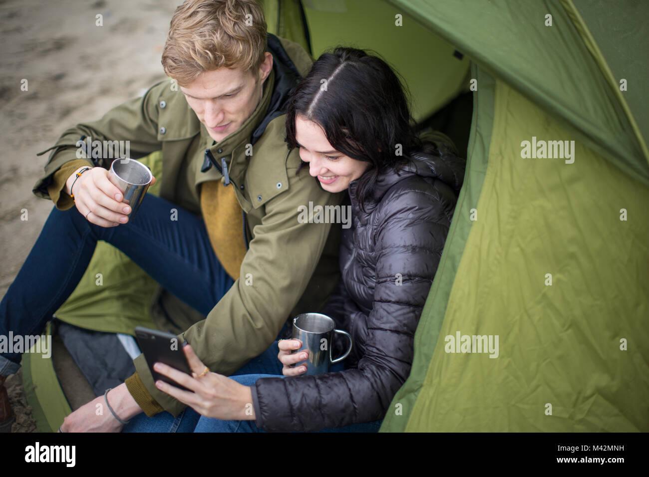 Jeune couple à l'aide d'un smartphone sur un voyage de camping Photo Stock