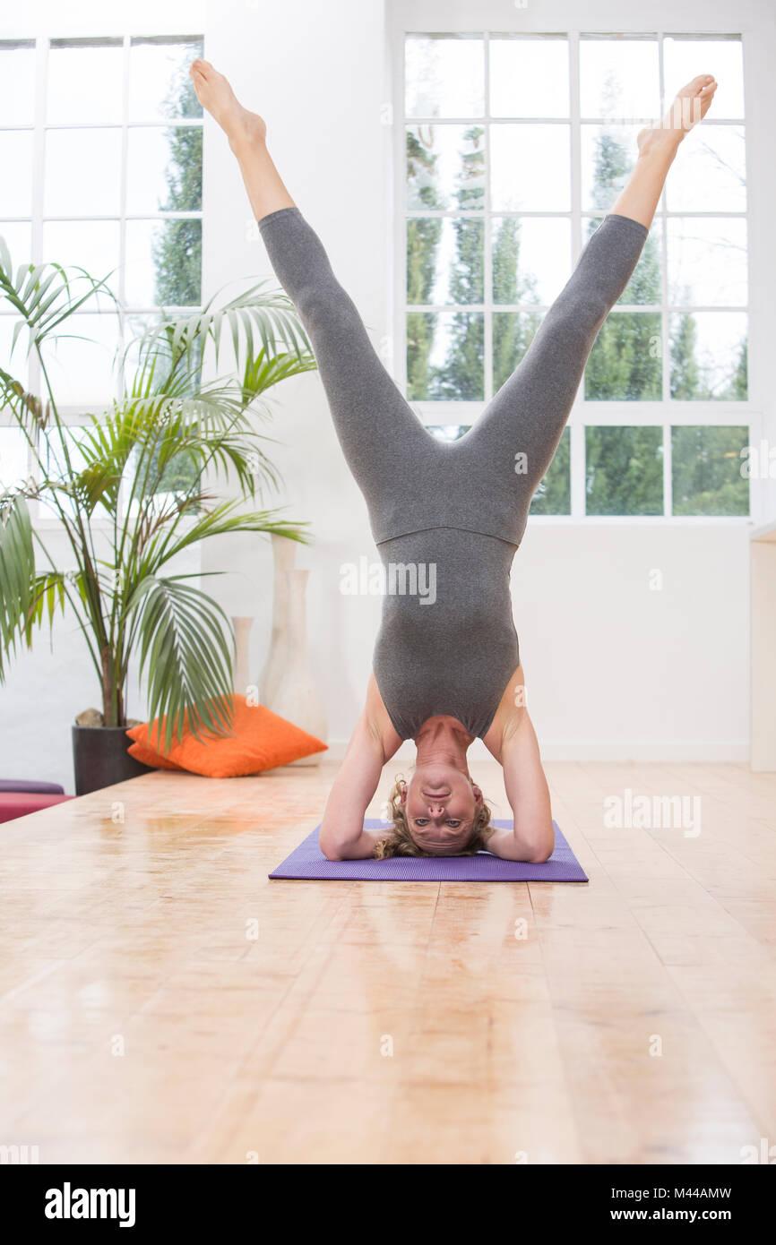 Femme au foyer, faire du yoga, faire la tête, in yoga position Banque D'Images