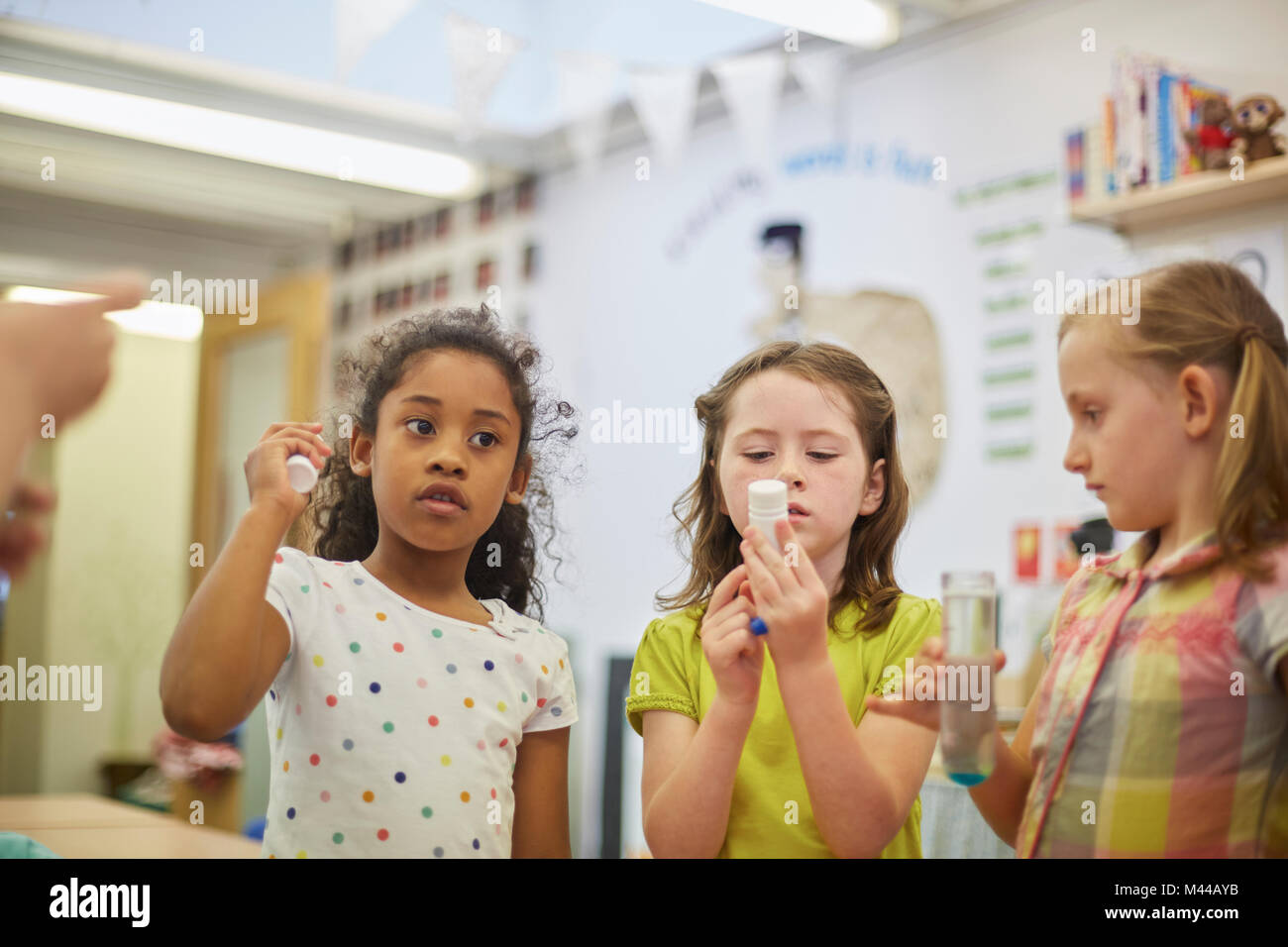 Ecolières primaire faisant expérimenter en classe Photo Stock
