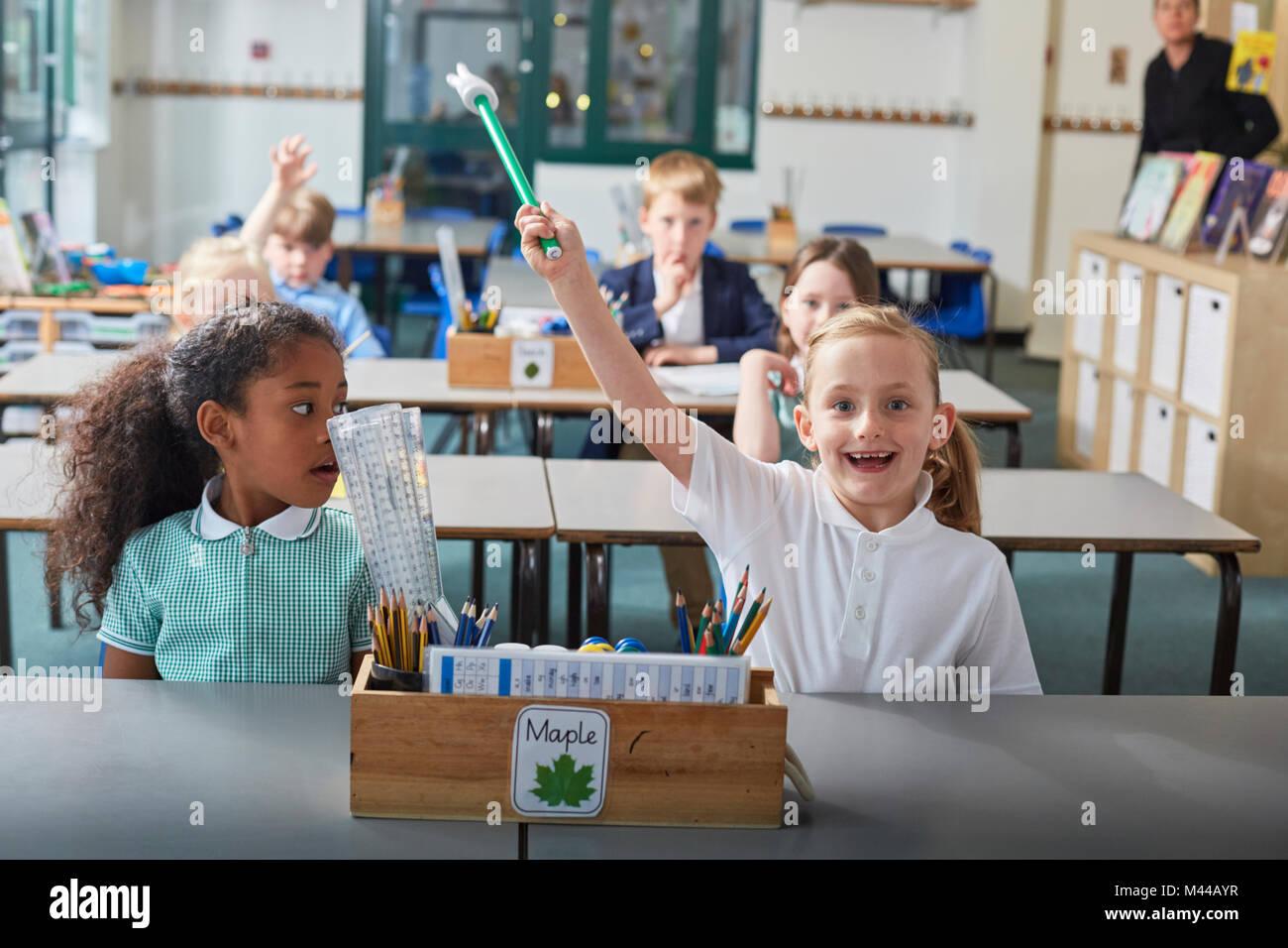 Écolière avec sa main posée à l'école primaire de la leçon en classe Photo Stock