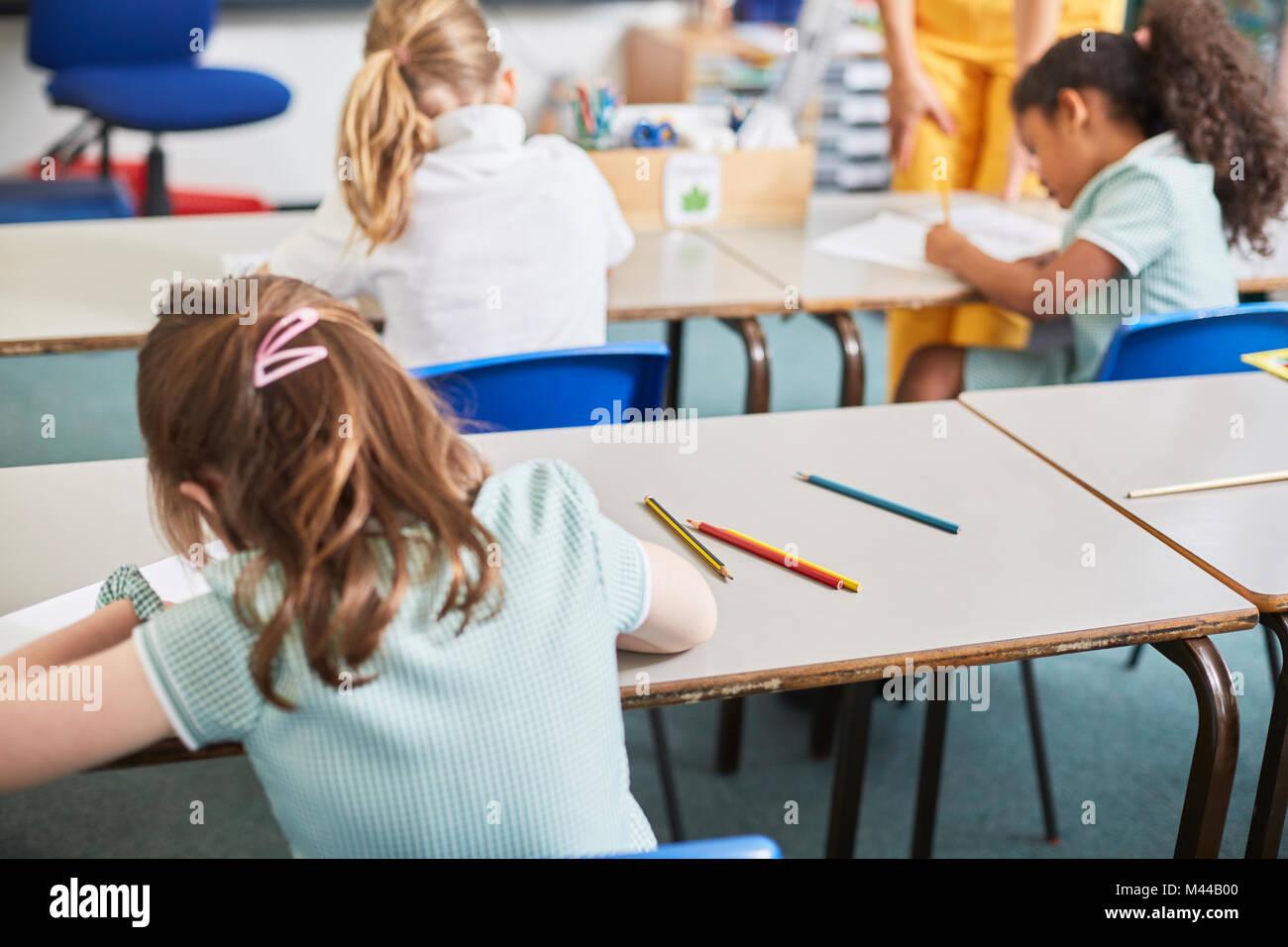 Lycéenne écrit au bureau de classe à l'école primaire leçon, vue arrière Banque D'Images