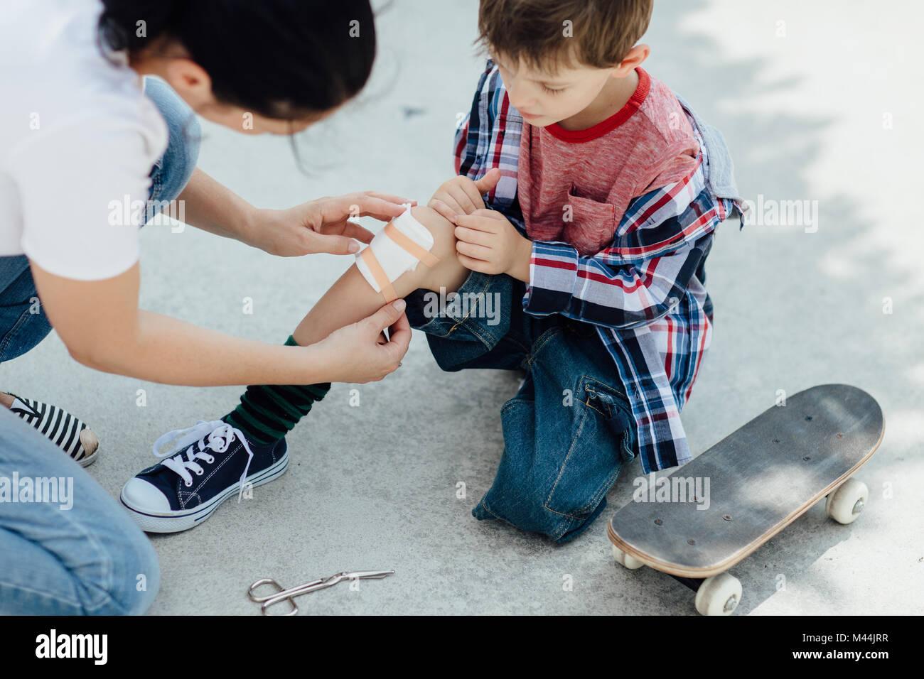 Les infirmières de la mère une saignée de son fils couper la planche à roulettes et met un plâtre Photo Stock