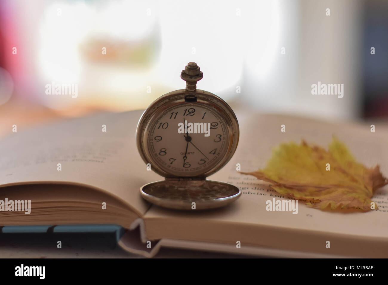 Ancienne montre de poche et livre ouvert sur la table/ Dimanche reposant et still life concept. Focus sélectif. Photo Stock