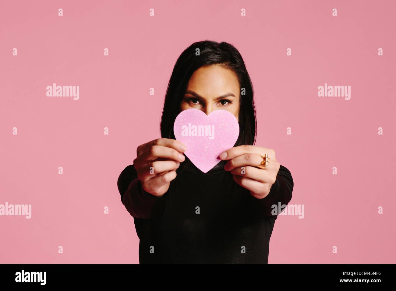 Woman in Black montrant coeur rose couvrant la moitié de son visage, être mon Valentin Photo Stock