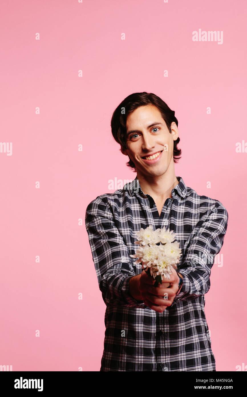 Sweet guy en chemise à carreaux et holding bouquet de fleurs blanches offrant Photo Stock