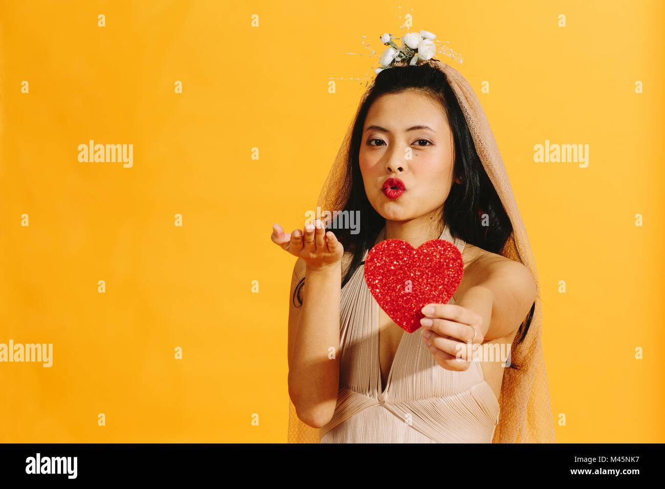 Mariée à souffler un baiser et un cœur rouge Photo Stock
