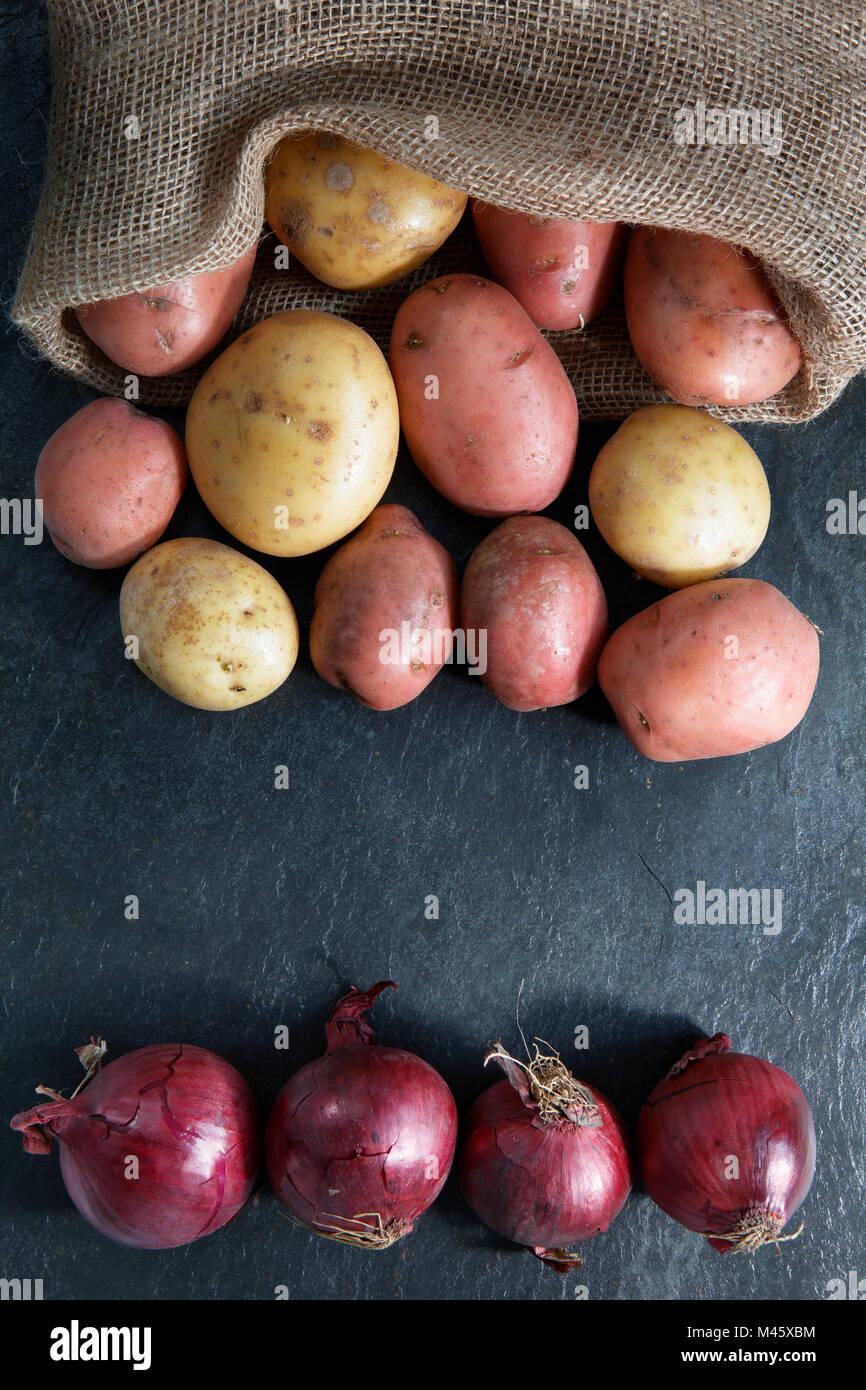 Pommes de terre rouge et or dans sac en toile de jute avec oignons rouges sur l'ardoise de table en l'espace Photo Stock