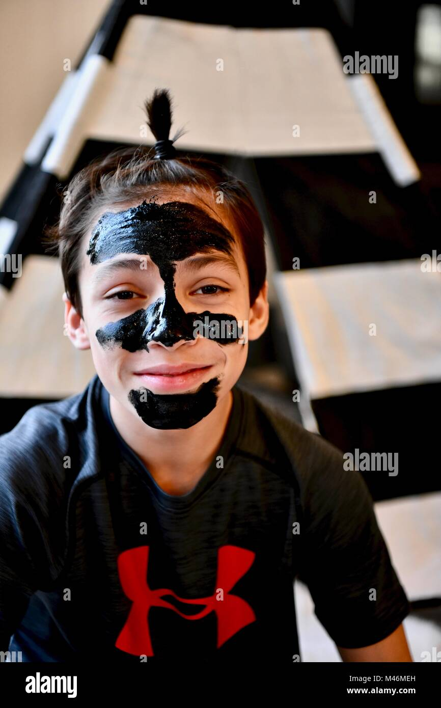 Teen boy wearing masque nettoyant facial noir Photo Stock