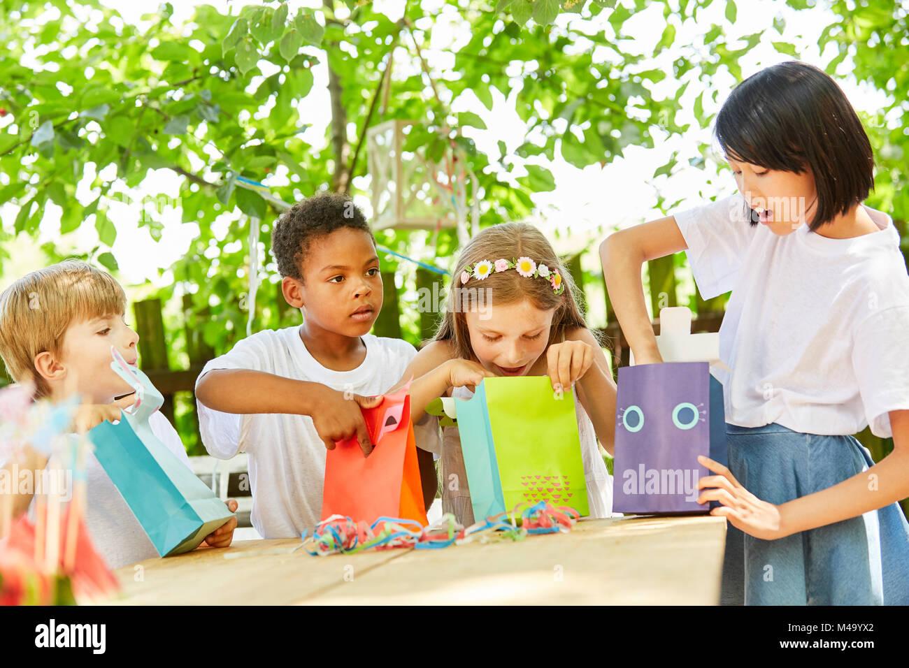 Groupe d'enfants déballage présente sur le mini anniversaire Photo Stock