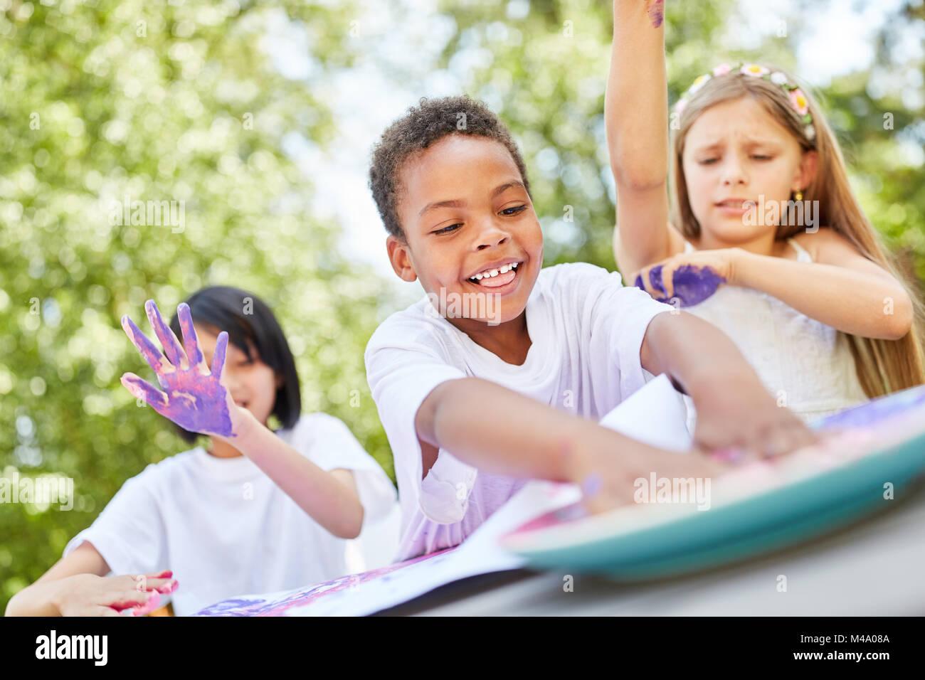 African boy joue avec les peintures et les peintures au doigt avec ses amis Photo Stock