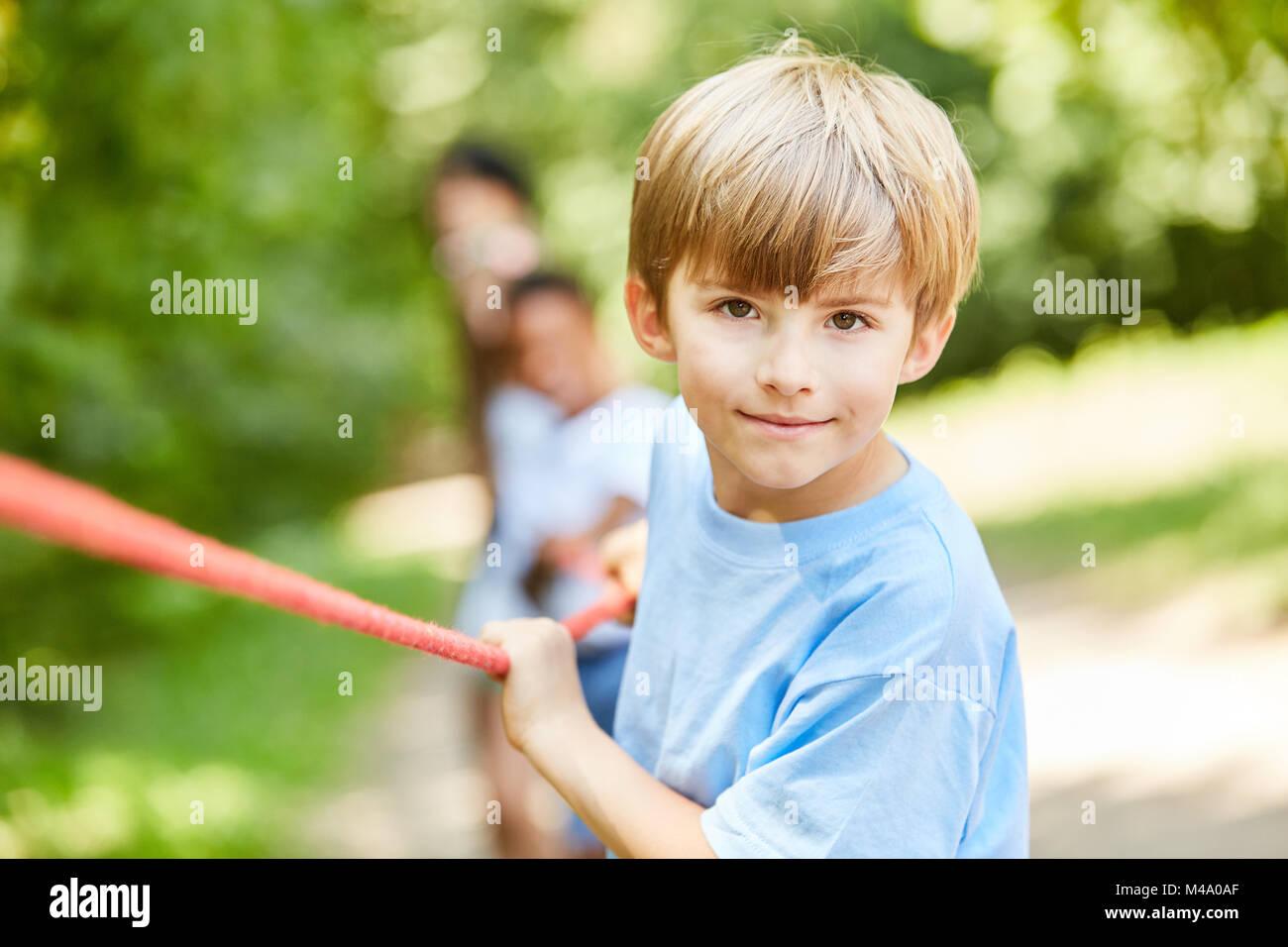 Déterminé à la corde garçon tirant sur la concurrence dans le camp d'été Photo Stock