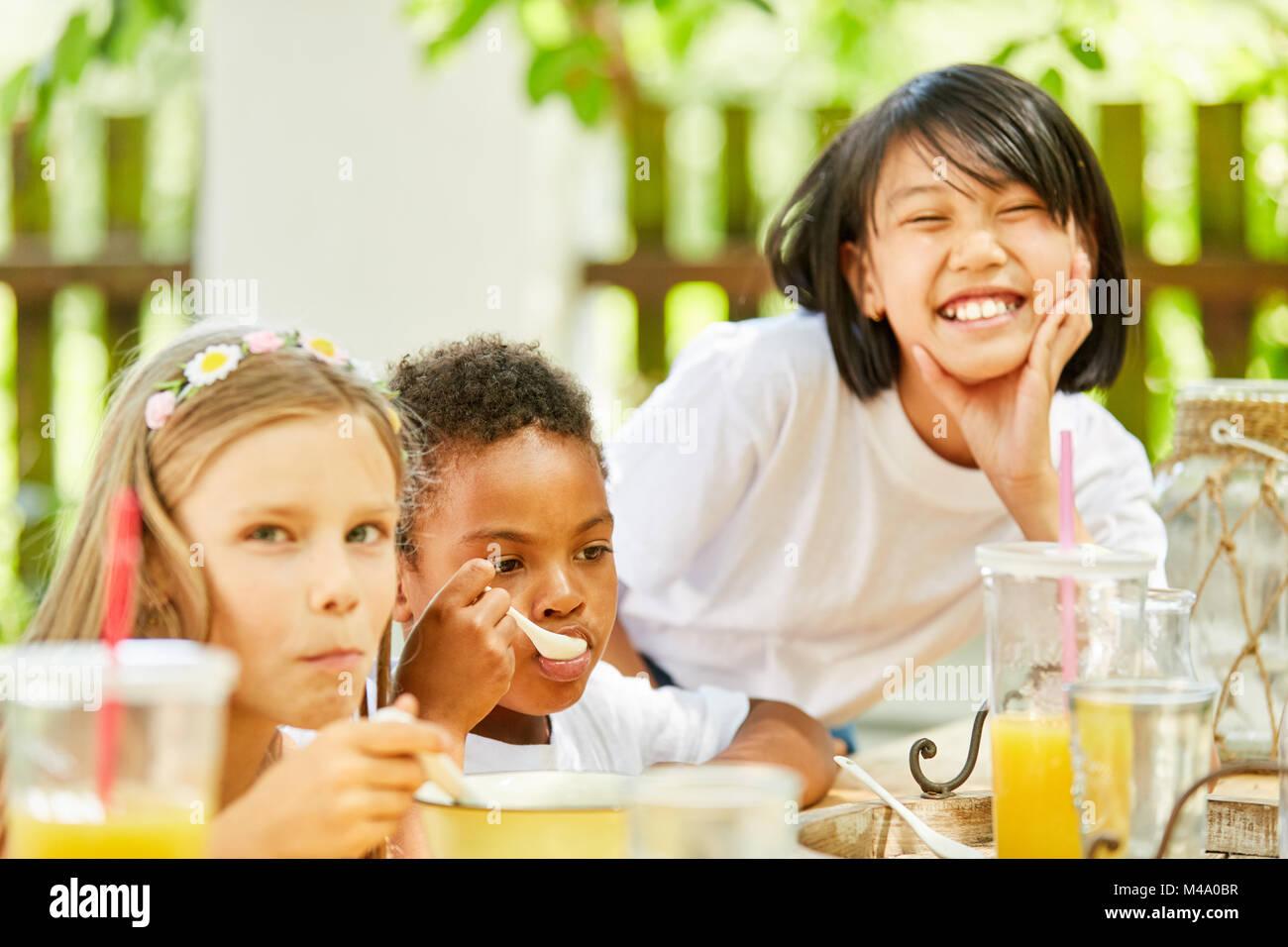 Les enfants dans la maternelle internationale prenant le petit déjeuner avec eux dans le jardin Photo Stock