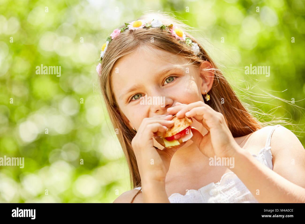 Fille avec des fleurs dans ses cheveux mange un pain baguette lors d'une fête Photo Stock