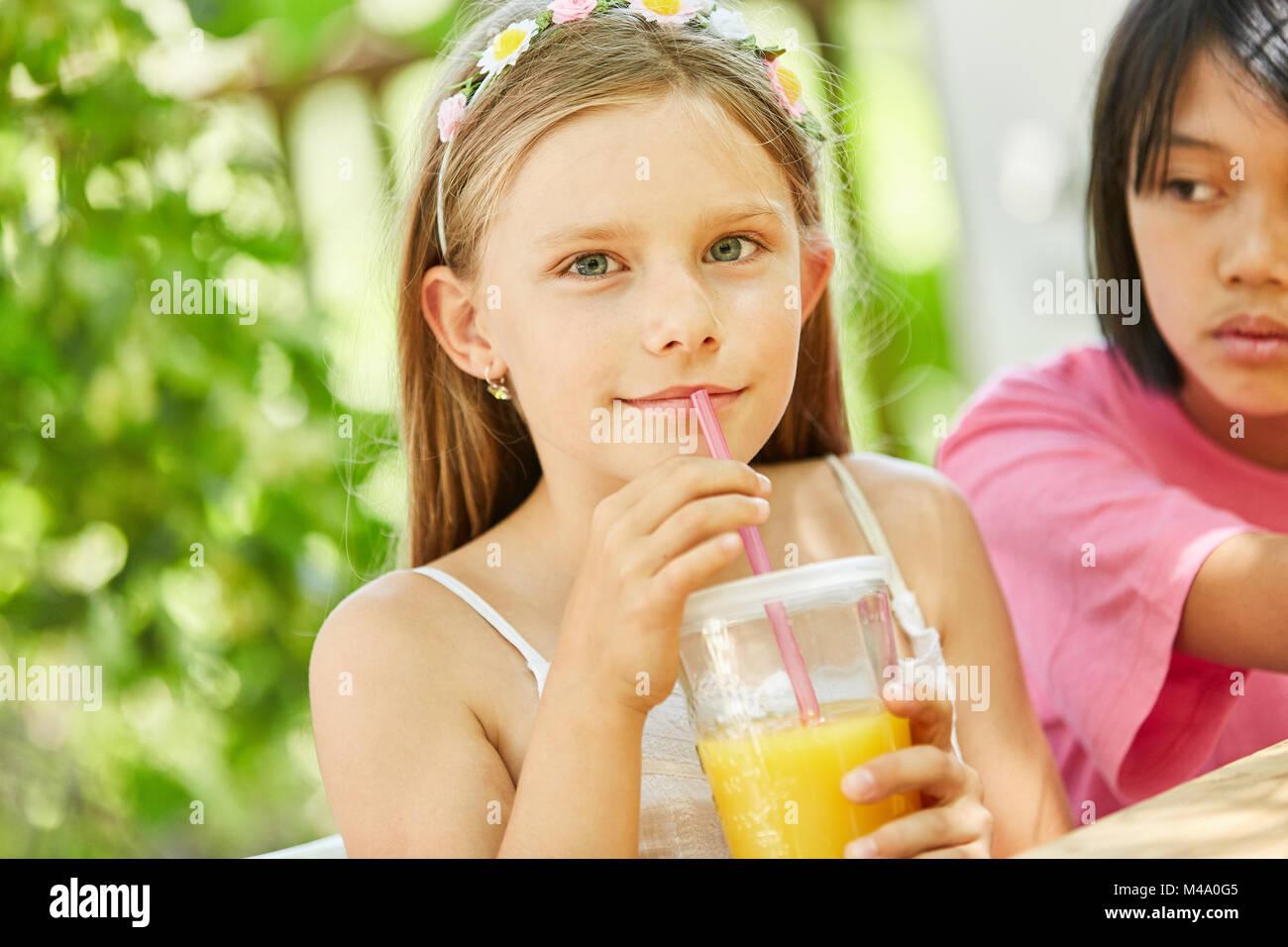 Girl boissons jus d'orange avec une paille pour le petit déjeuner Photo Stock