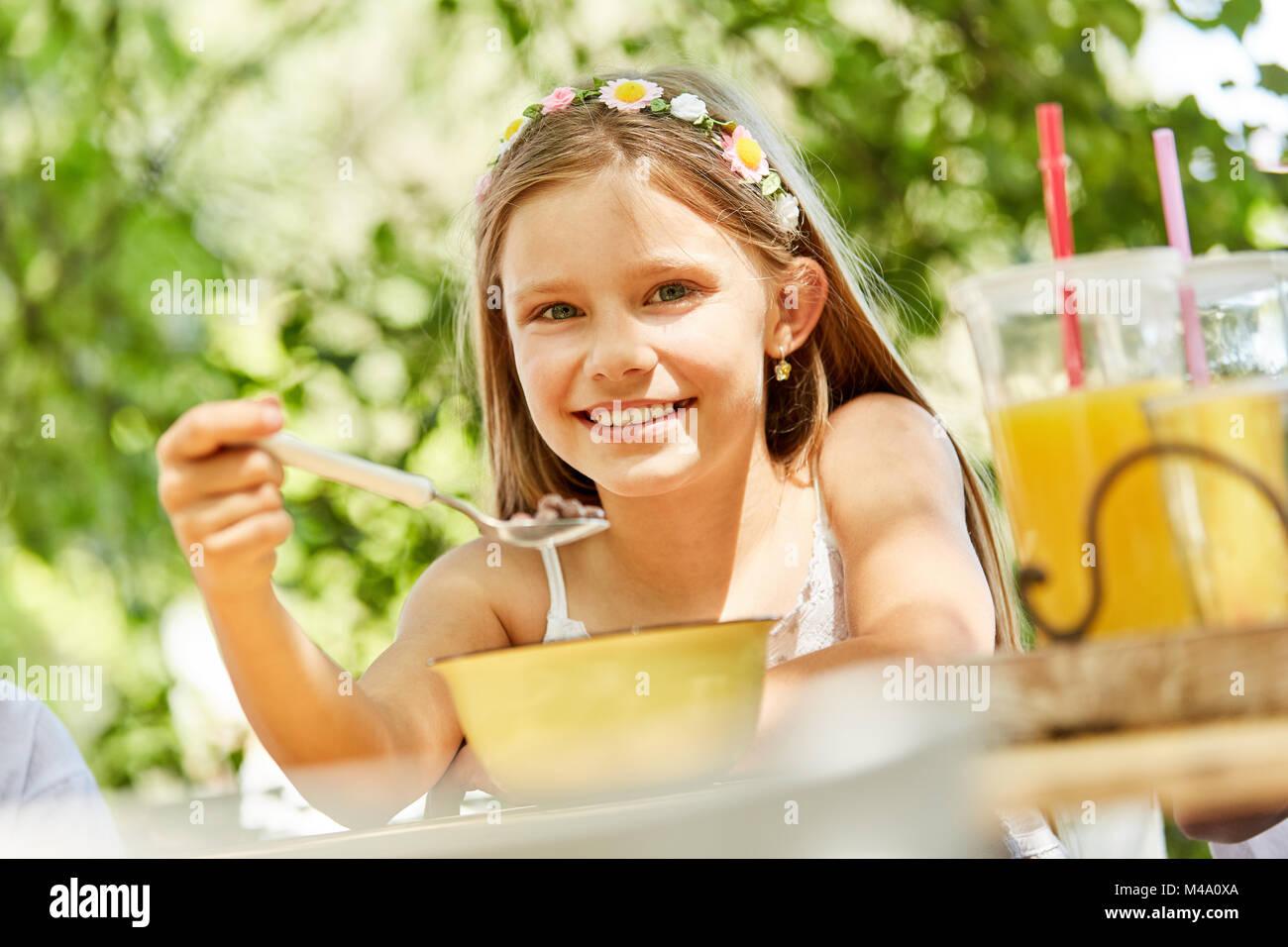 Smiling girl est de manger sain pour le petit déjeuner céréales en summer camp Photo Stock