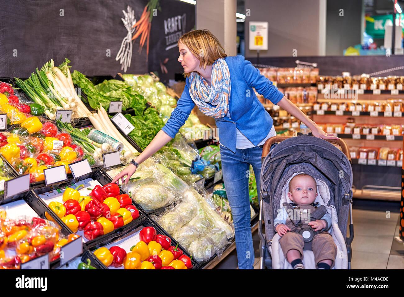 La femme en bleu veste et jeans comment choisir les légumes Photo Stock