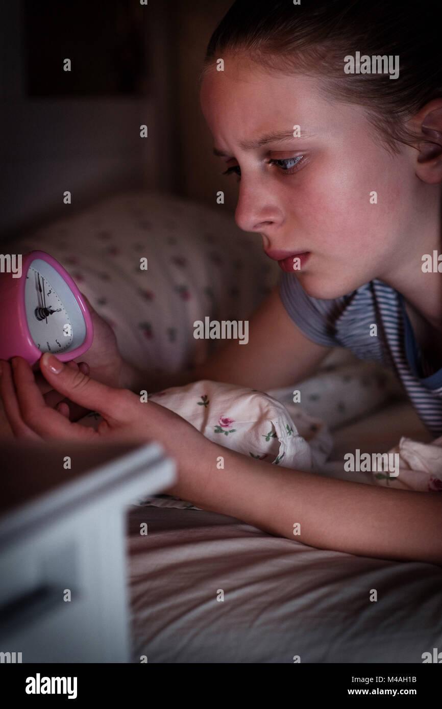 Fille anxieuse incapable de dormir la nuit à la recherche au réveil Photo Stock