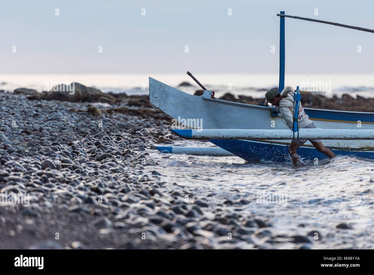 Pêcheur balinais est de retour de la pêche et pousse sa pirogue (Jukung) à la plage de gravier Banque D'Images