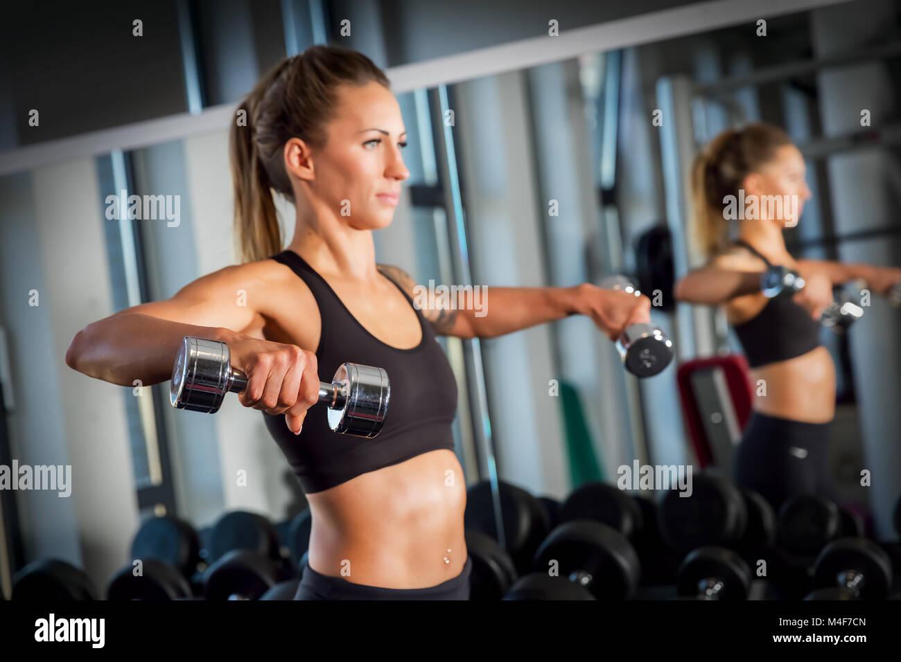 Jolie femme haltérophilie dans la salle de sport. Photo Stock