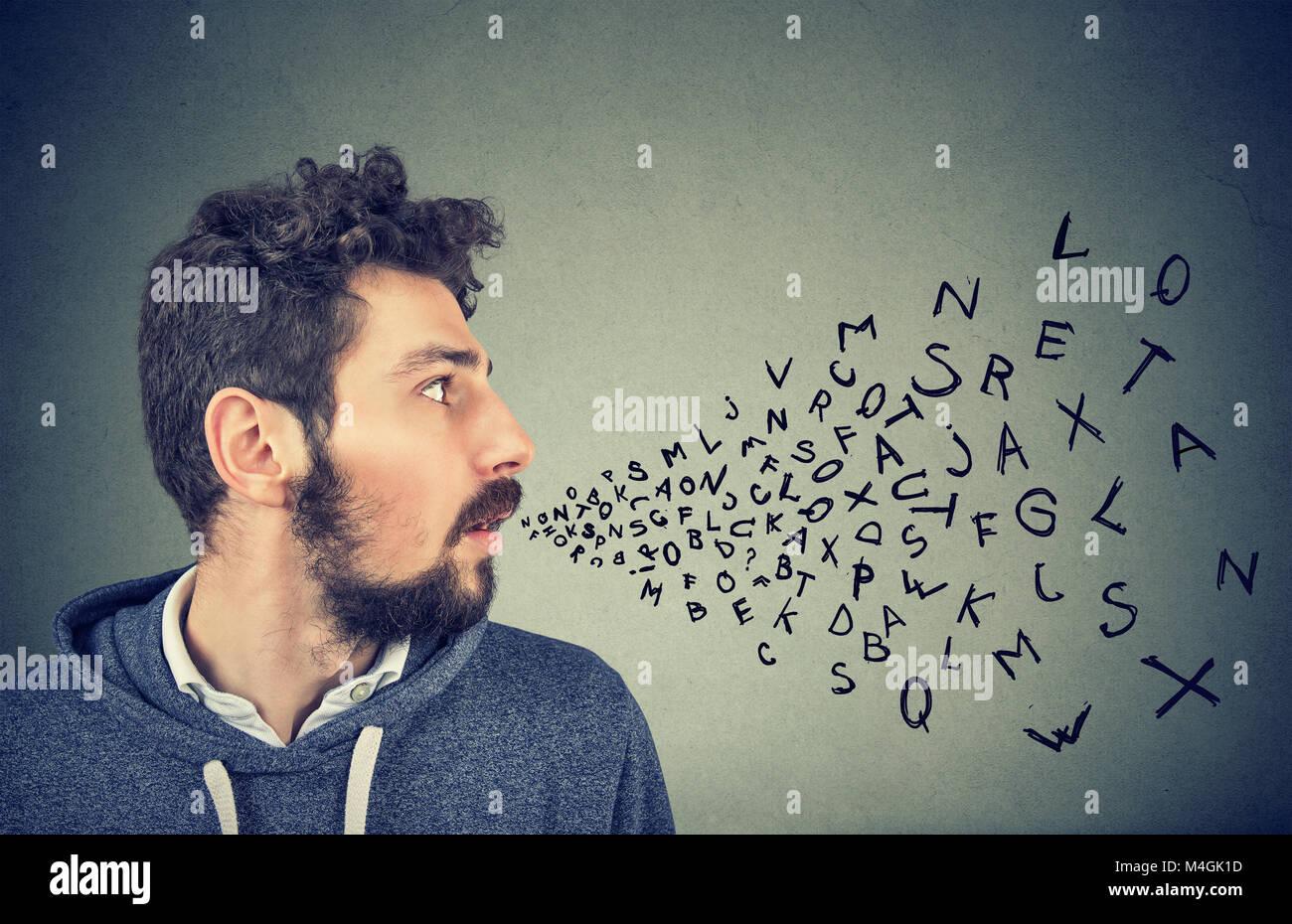 L'homme parlant avec lettres de l'alphabet qui sortent de sa bouche. Communication, information, intelligence Photo Stock