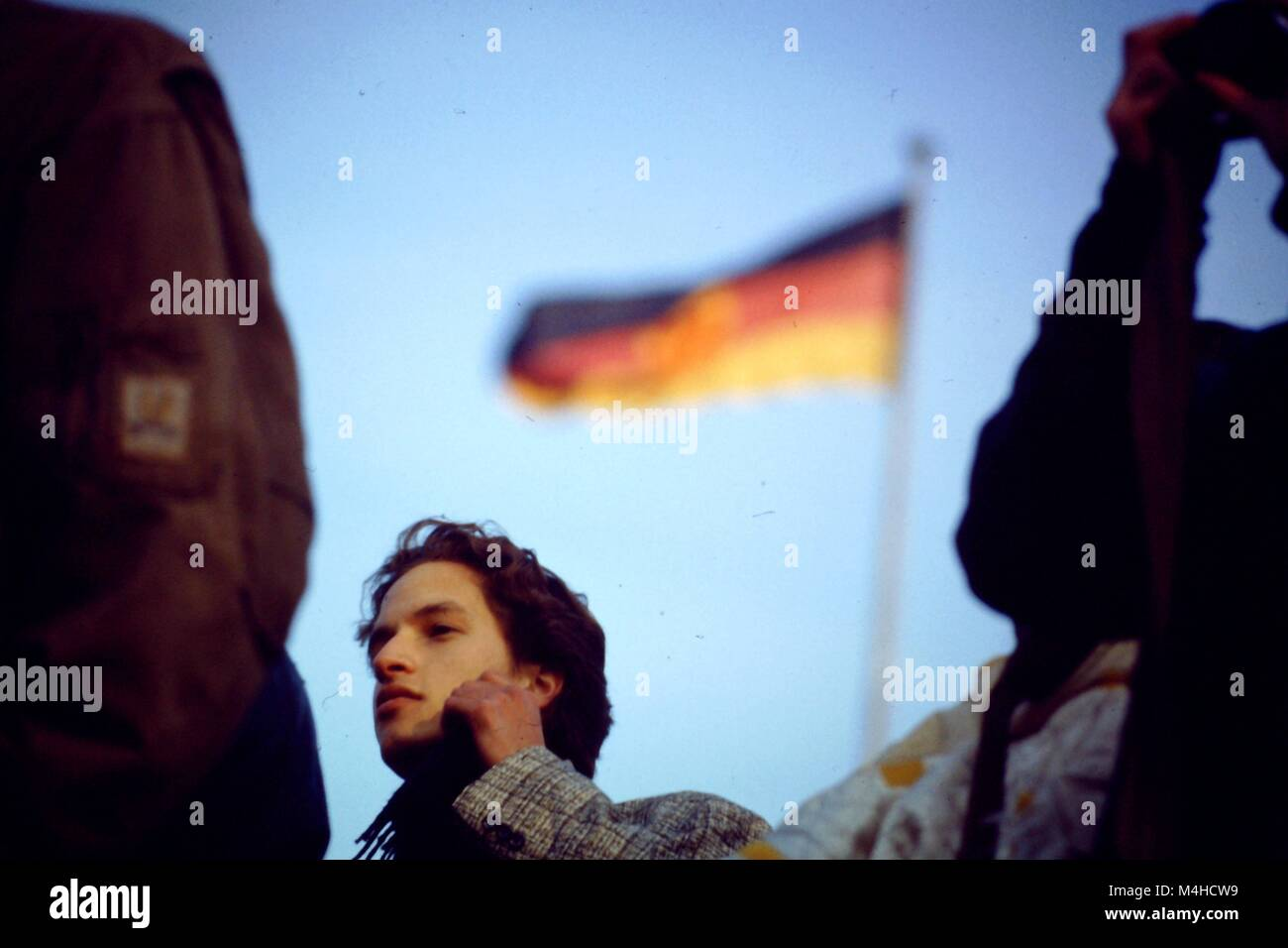 Un jeune homme, visiblement surpris par la chute du Mur de Berlin, debout devant un drapeau de la RDA à Berlin. Photo Stock