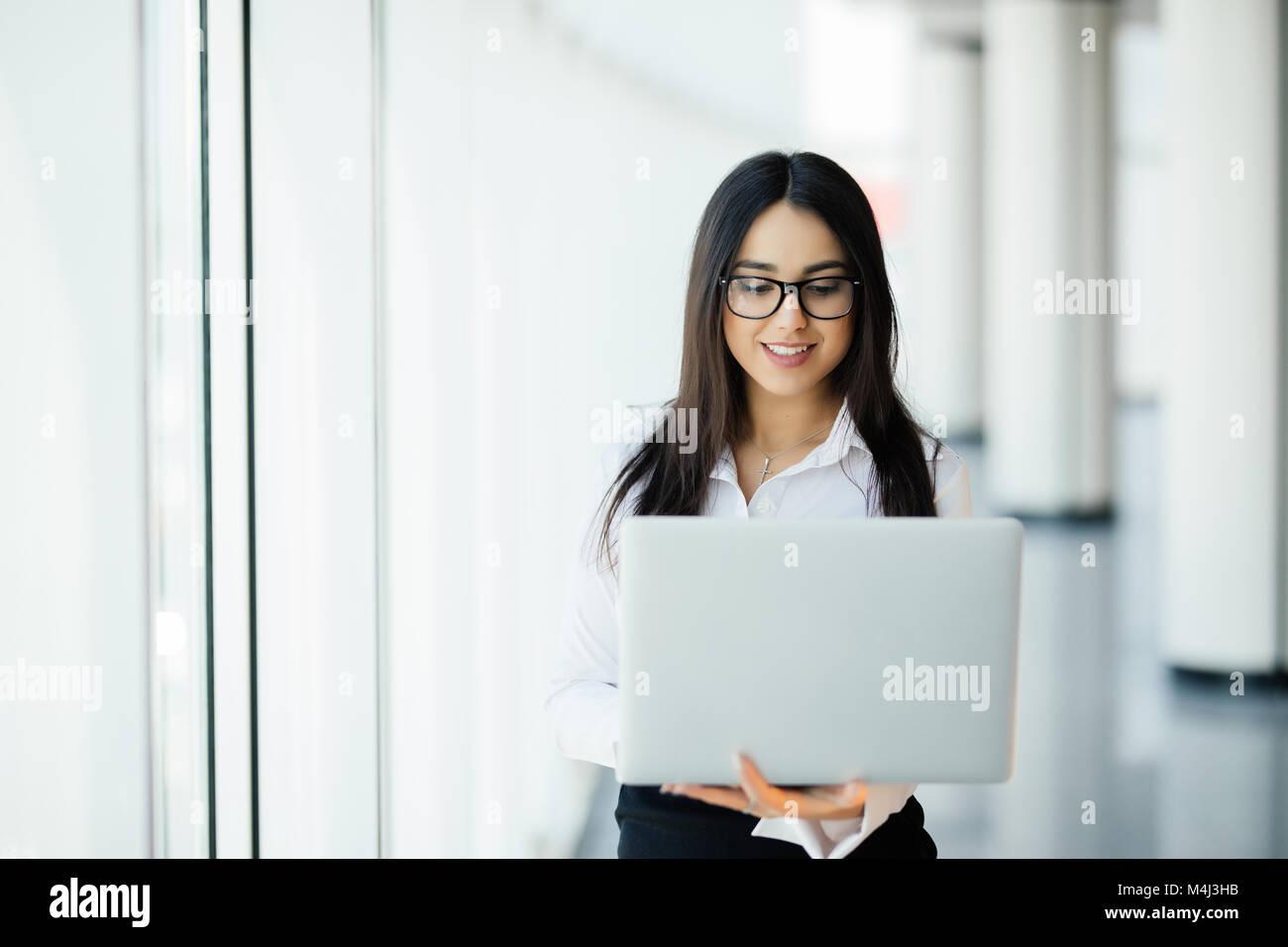 Portrait of young woman holding laptop debout contre la fenêtre panoramique avec vue sur la ville Banque D'Images