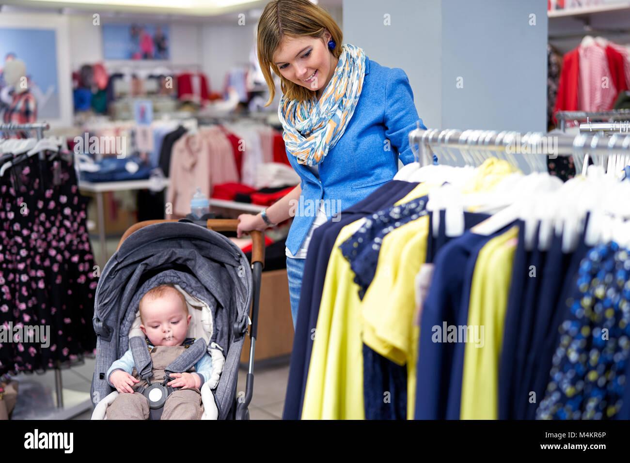 Jeune femme choisit des vêtements dans un magasin Photo Stock