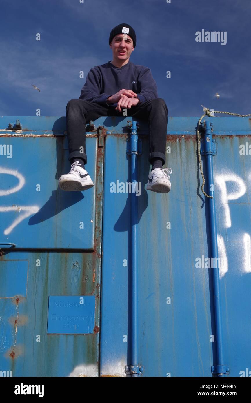 Jeune homme assis au sommet d'un ancien bleu contenant d'expédition au port Bay Cruden, Aberdeenshire, Scotland, UK. L'hiver, en 2018. Banque D'Images