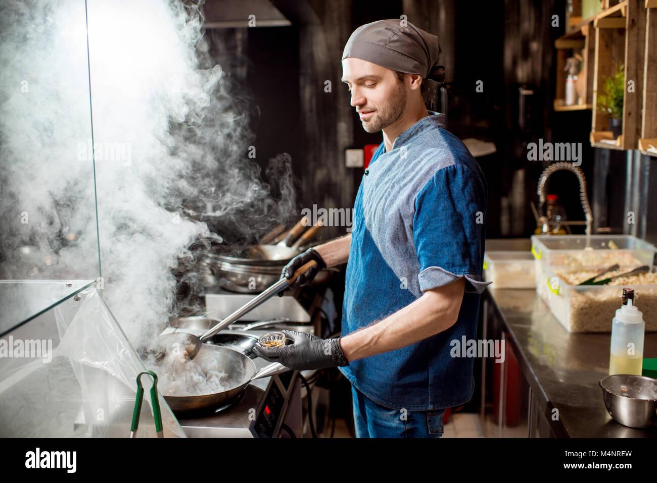 Le cuisinier en chef de cuisine dans la cuisine asiatique Photo Stock