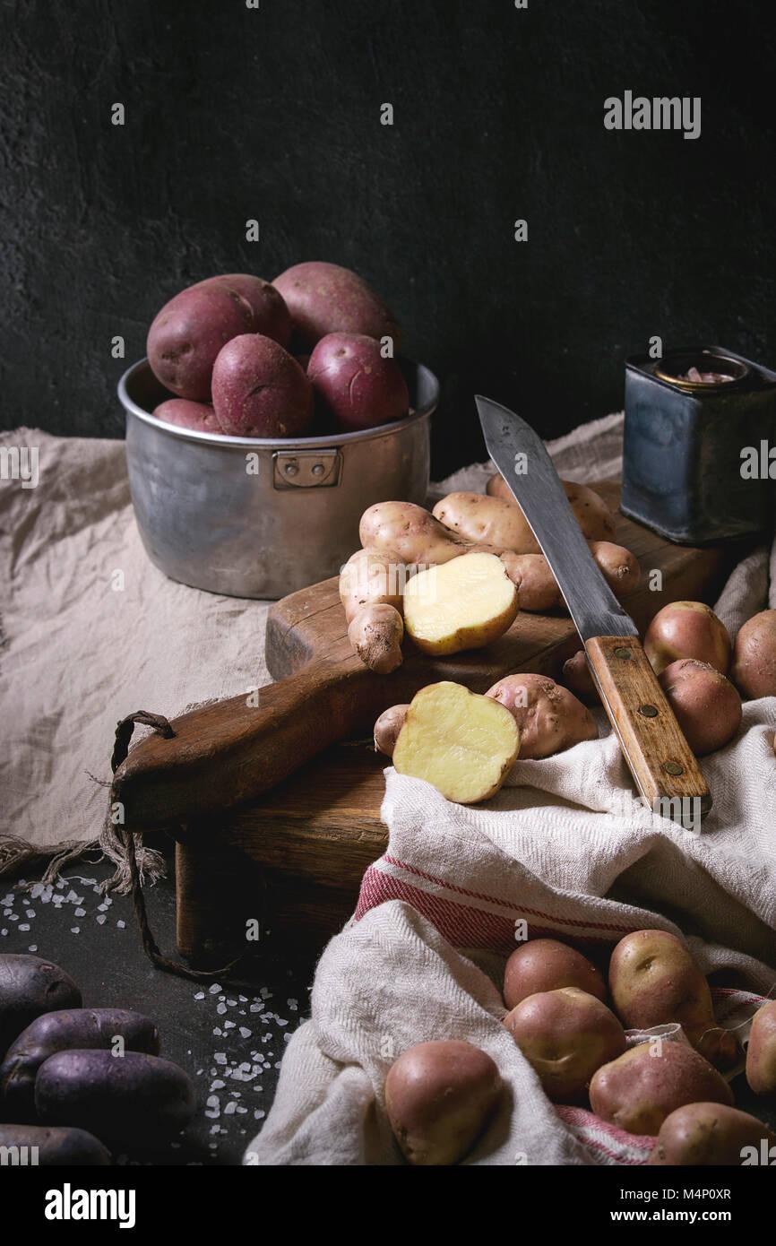 Variété de matières organiques non cuits pommes de différents types et couleurs rouge, jaune, violet sur planche Banque D'Images