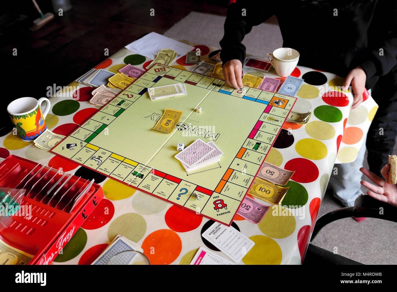 Jeu de Monopoly joué par les enfants dans une maison d'amis sur une table avec nappe colorée à mi-terme dans Carmarthenshire Wales UK Banque D'Images