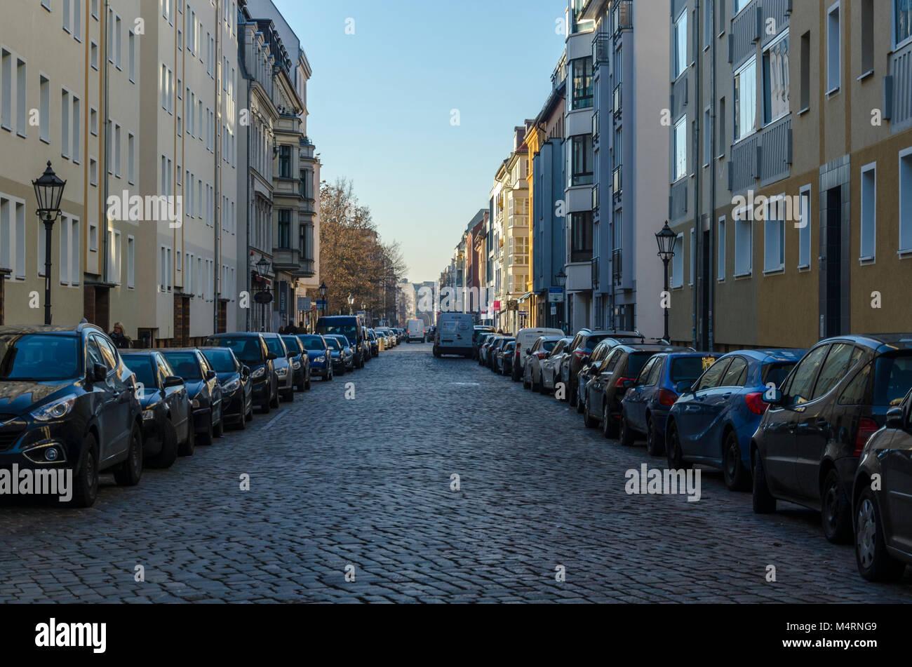Voitures garées dans une rue pavée à Berlin, Allemagne Photo Stock