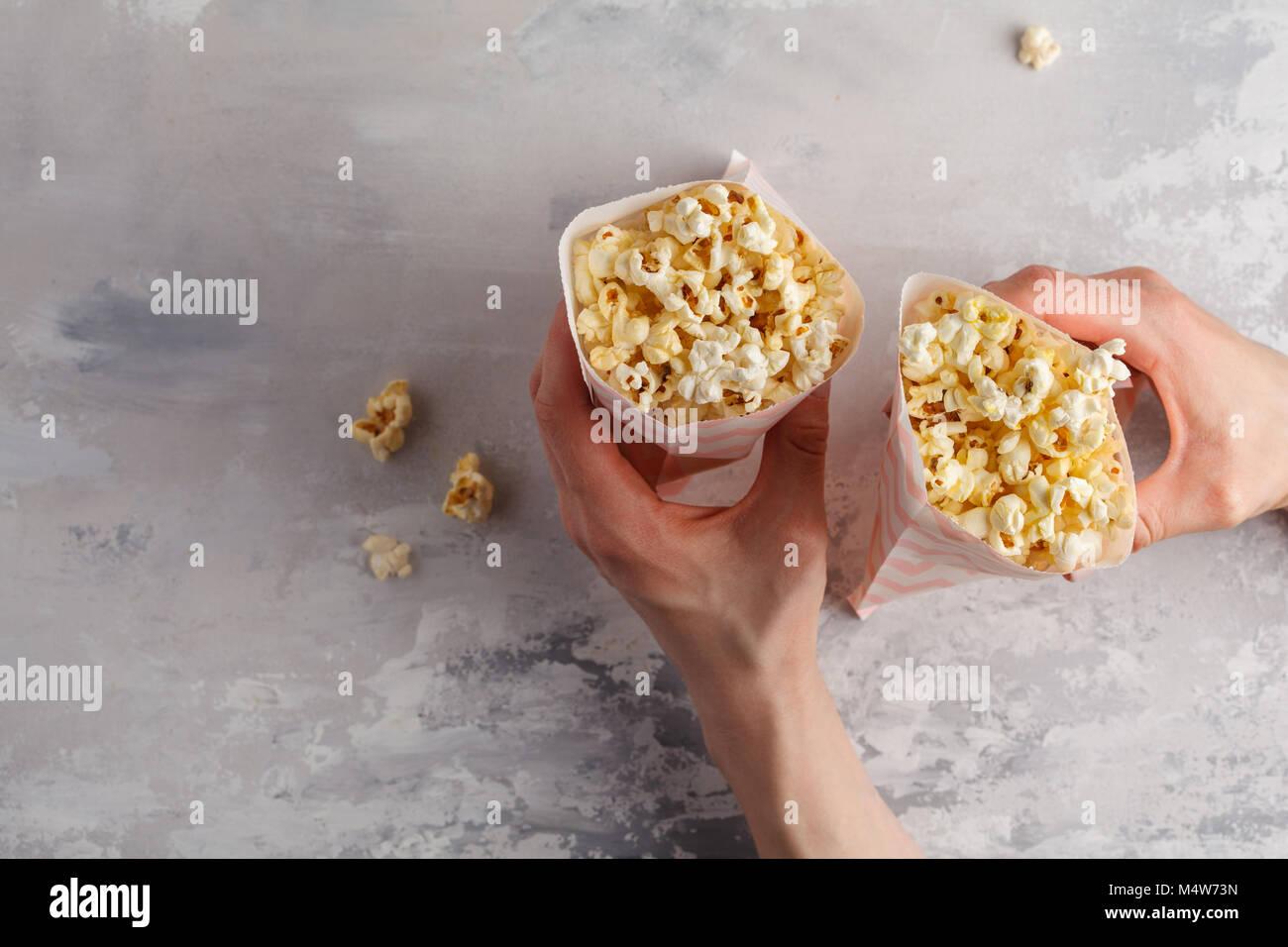Pop corn caramel doré dans des sacs en papier dans les mains, vue d'en haut. Photo Stock