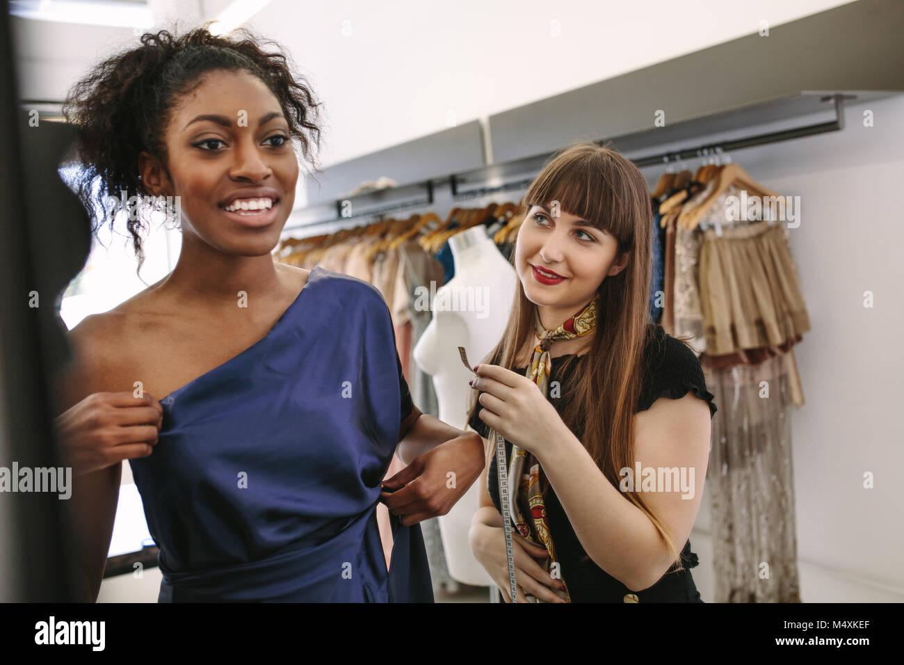 L'essai de nouveaux modèles de vêtements de créateurs dans une boutique. Femme entrepreneur dans Photo Stock