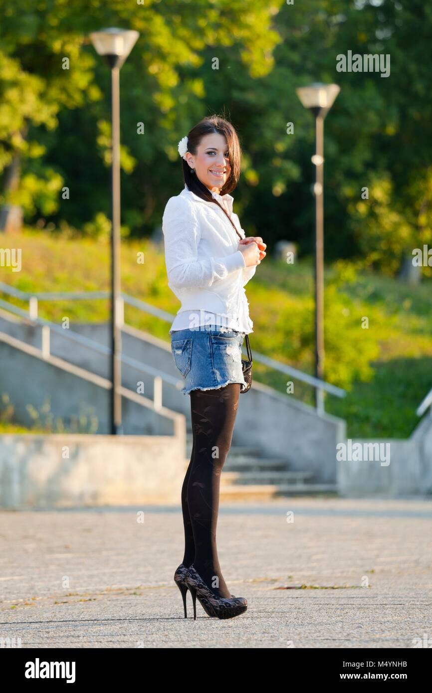 Jeune femme jambes talons jupe courte denim Photo Stock