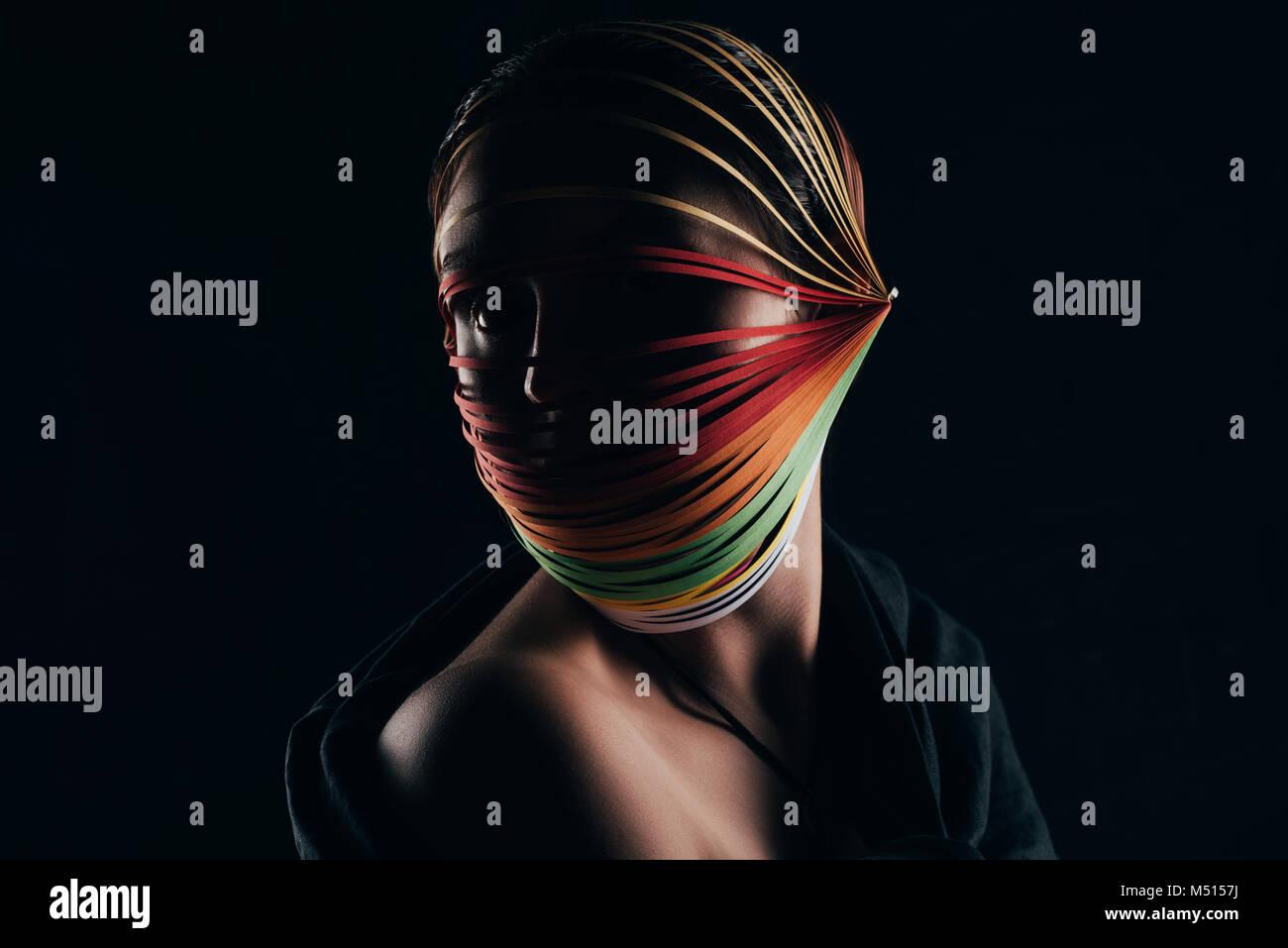 Femme avec du papier de couleur à la tête de canetage loin isolated on black Banque D'Images