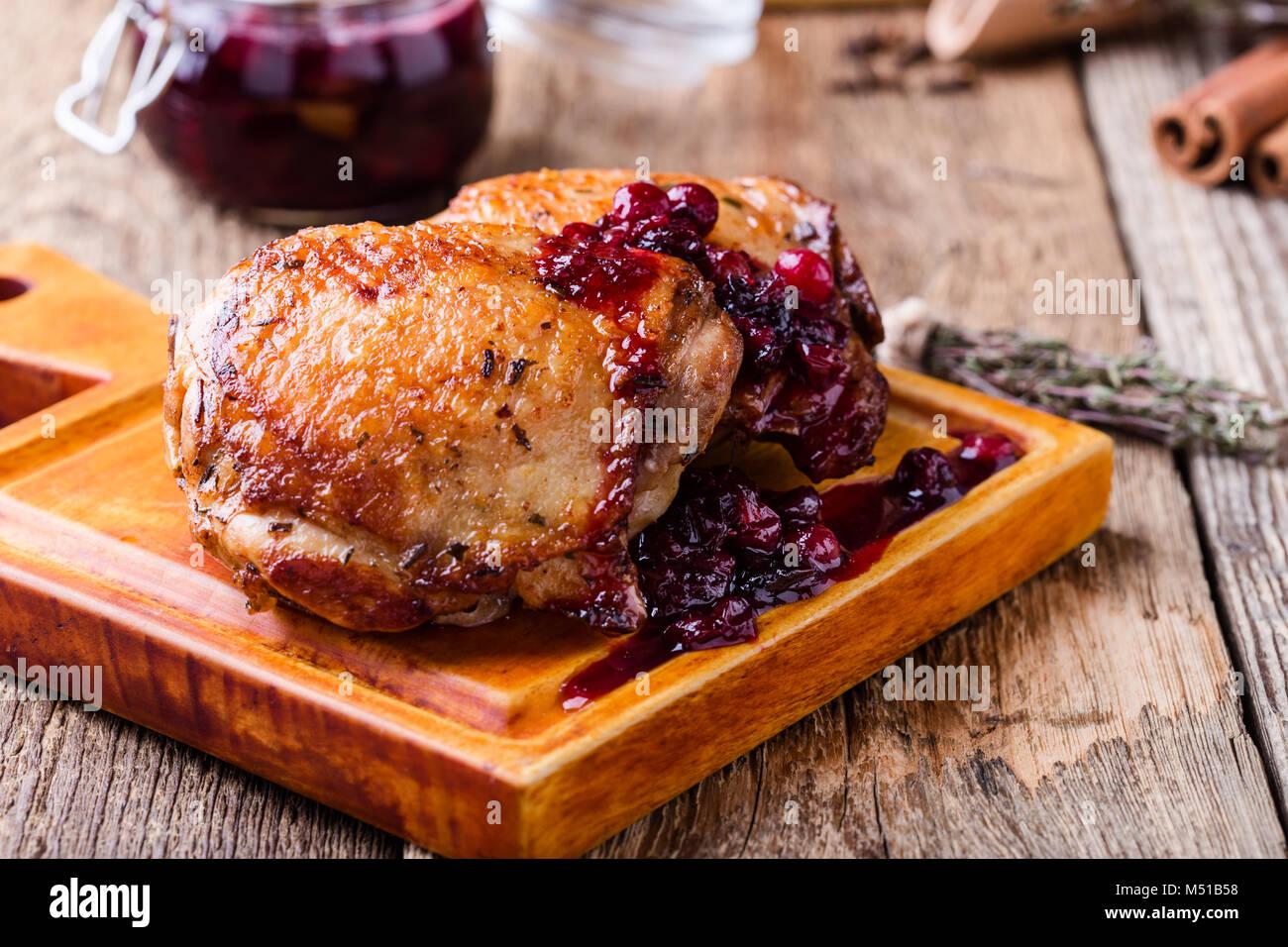 Cuisses de poulet rôti sur une planche à découper sauce canneberge sur table en bois rustique Photo Stock