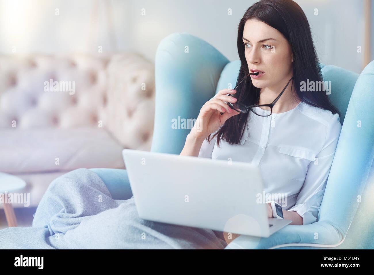 Épuisé brunette pense tout en travaillant de chez vous. Photo Stock