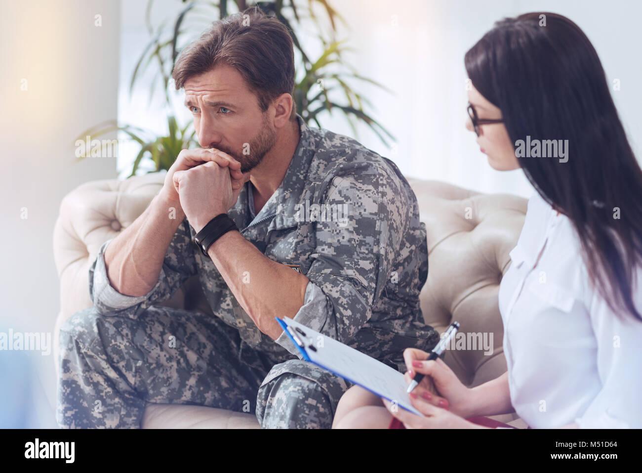 Soldat pensif rappelant des mémoires de guerre au psychothérapeute femelle Photo Stock