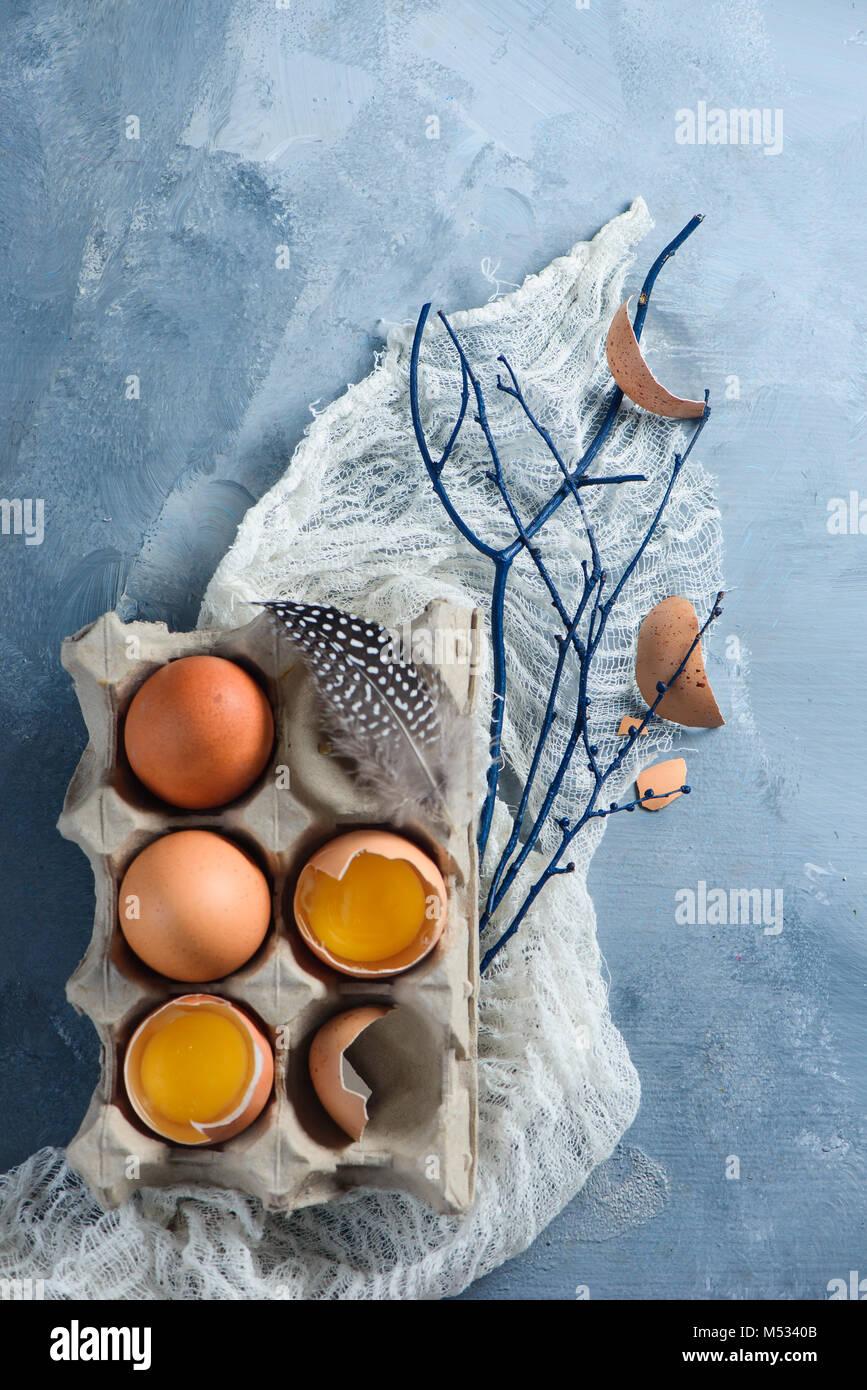 Décorations de Pâques avec des oeufs frais concept dans un carton, des branches d'arbre et de l'étoffe Photo Stock