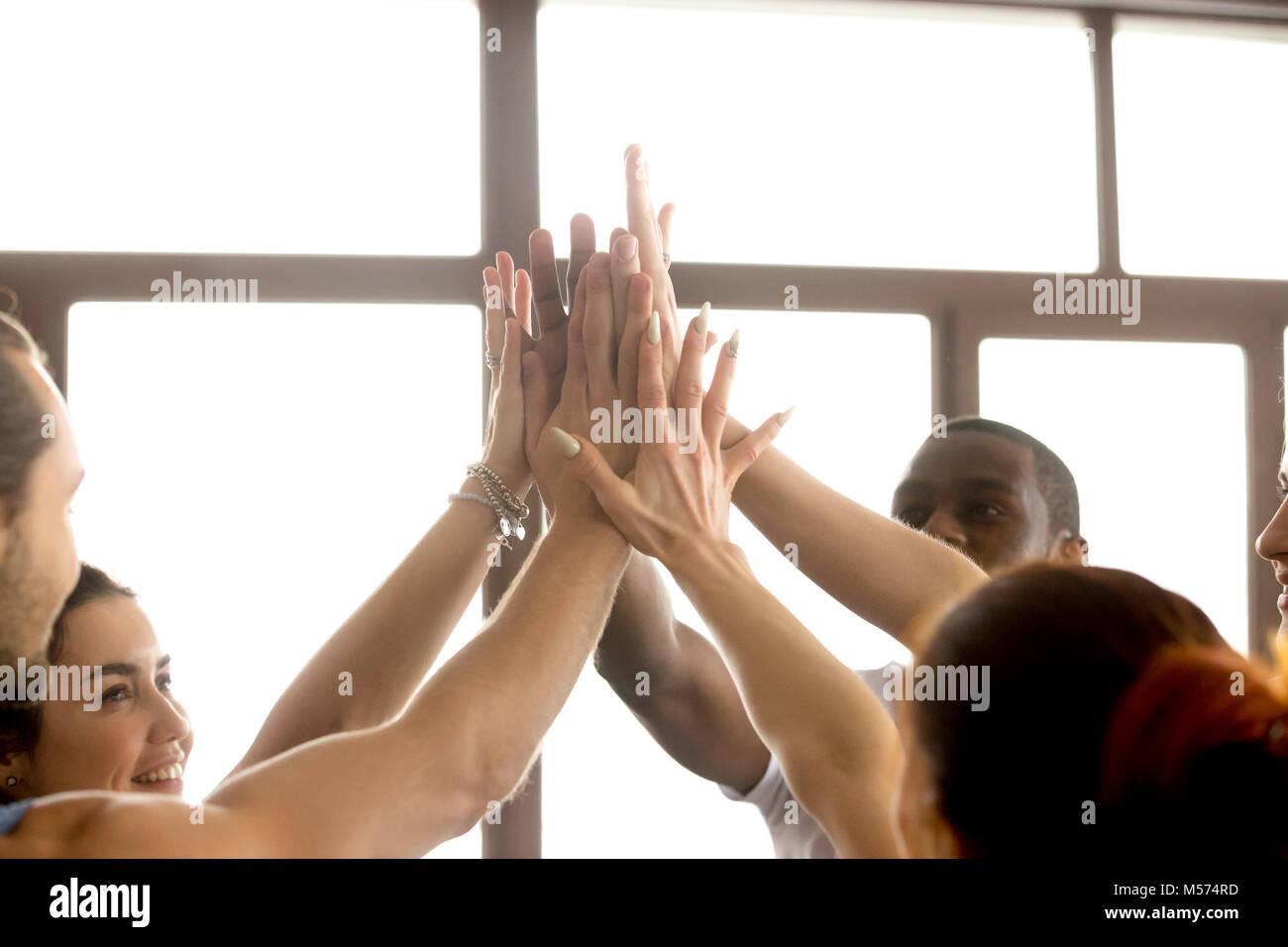 L'équipe multi-ethnique motivés de rejoindre les mains ensemble, offrant un rapport f Photo Stock