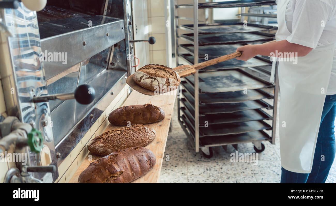 Femme de mettre du pain Boulangerie pâtisserie à bord avec pelle Banque D'Images