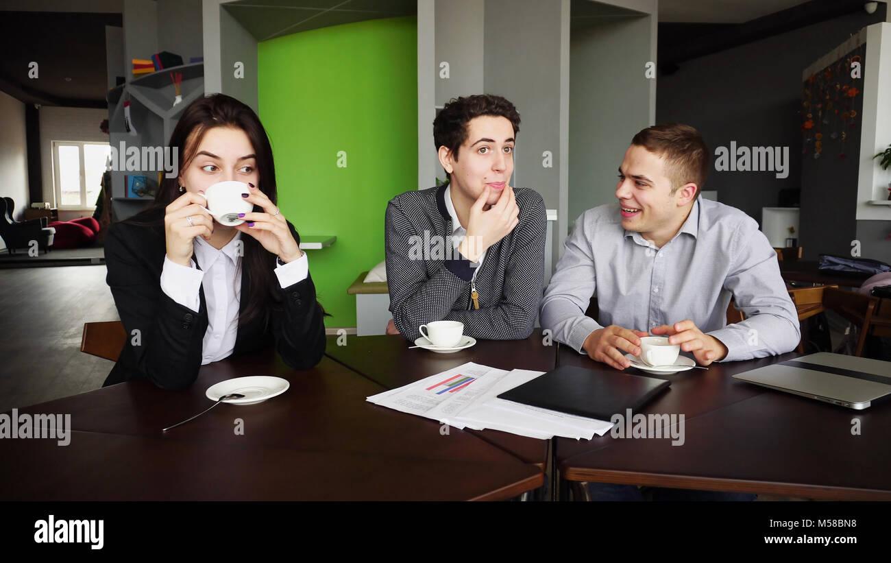 Trois jeunes gestionnaires, femme et deux hommes sur le chat et de repos Banque D'Images