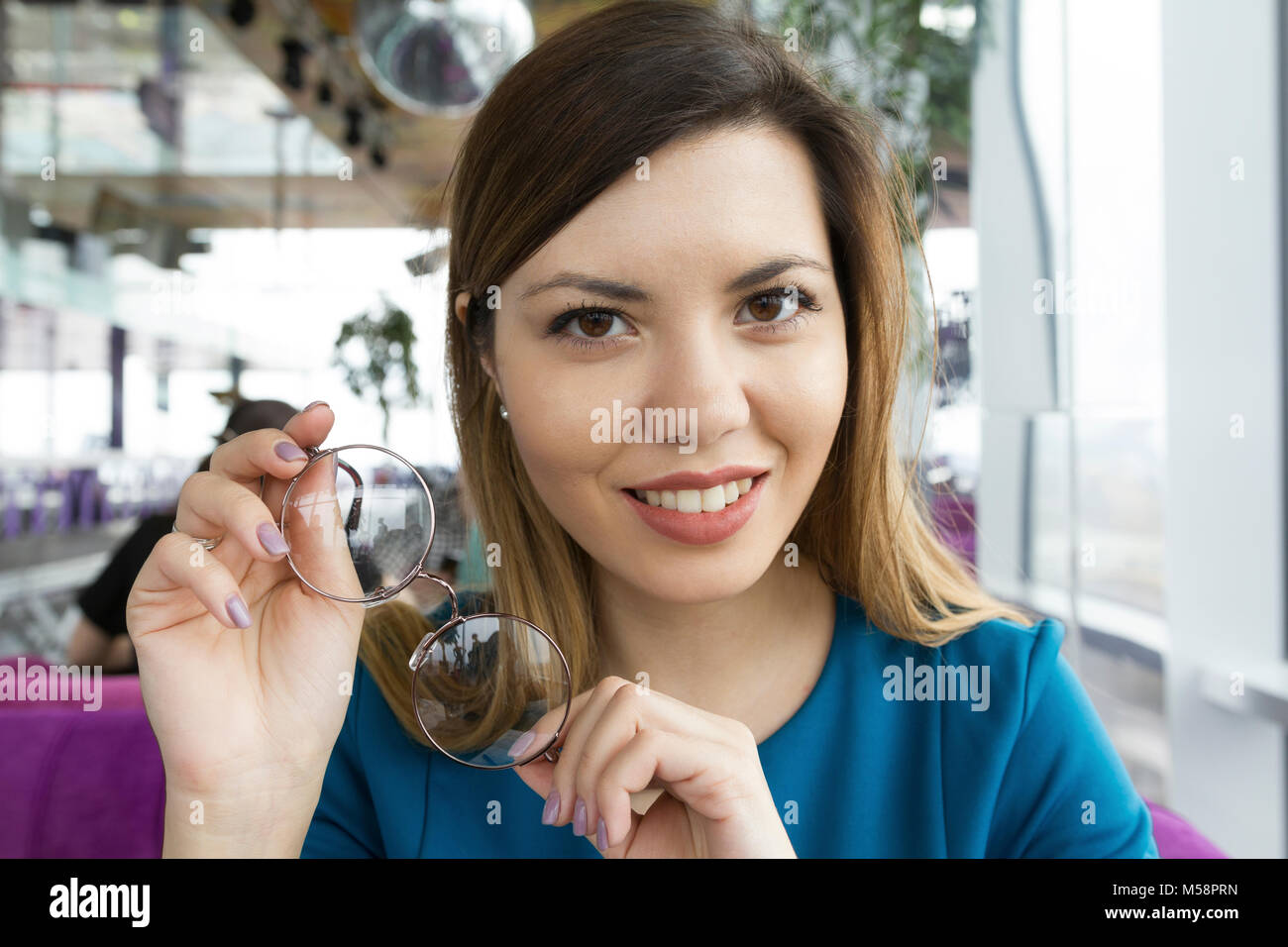 Happy young girl sitting in a cafe Photo Stock