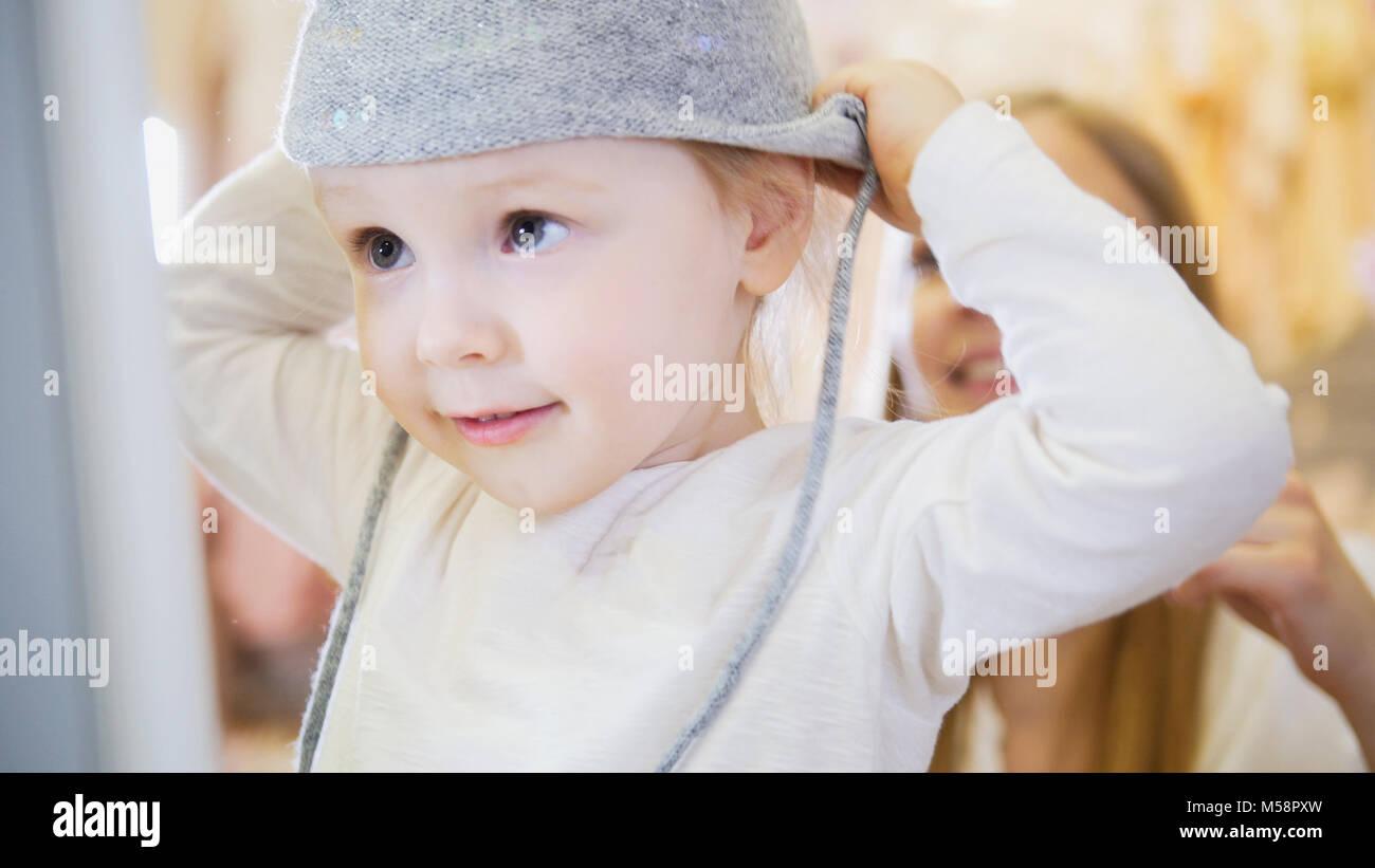 ce2ce3d857609 La petite fille en face d un miroir portant un bonnet gris. Photo Stock