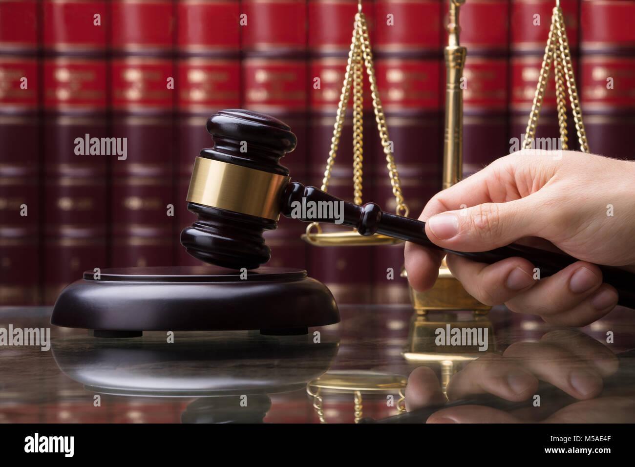 Close-up d'une main humaine Maillet frappant en face de l'échelle de pesage d'Or Banque D'Images